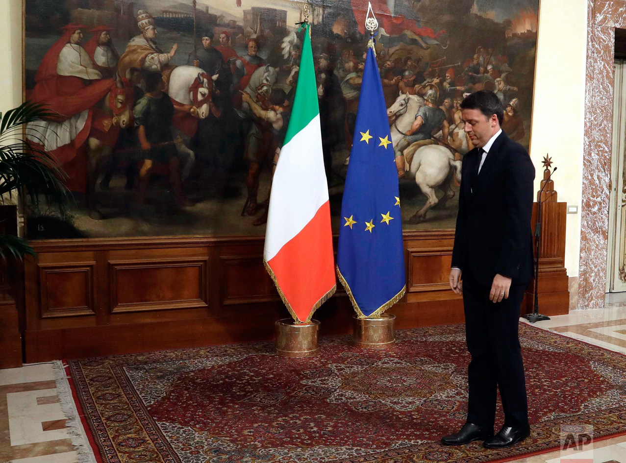 In this Monday, Dec. 12, 2016 photo, Italian outgoing Premier Matteo Renzi, right, waits for new Premier Paolo Gentiloni prior to the handover ceremony at Chigi Palace Premier's office, in Rome. Paolo Gentiloni, a Democrat serving as foreign minister, formed Italy's new government Monday, keeping several key ministers from the coalition of Matteo Renzi, who resigned last week. (AP Photo/Gregorio Borgia)