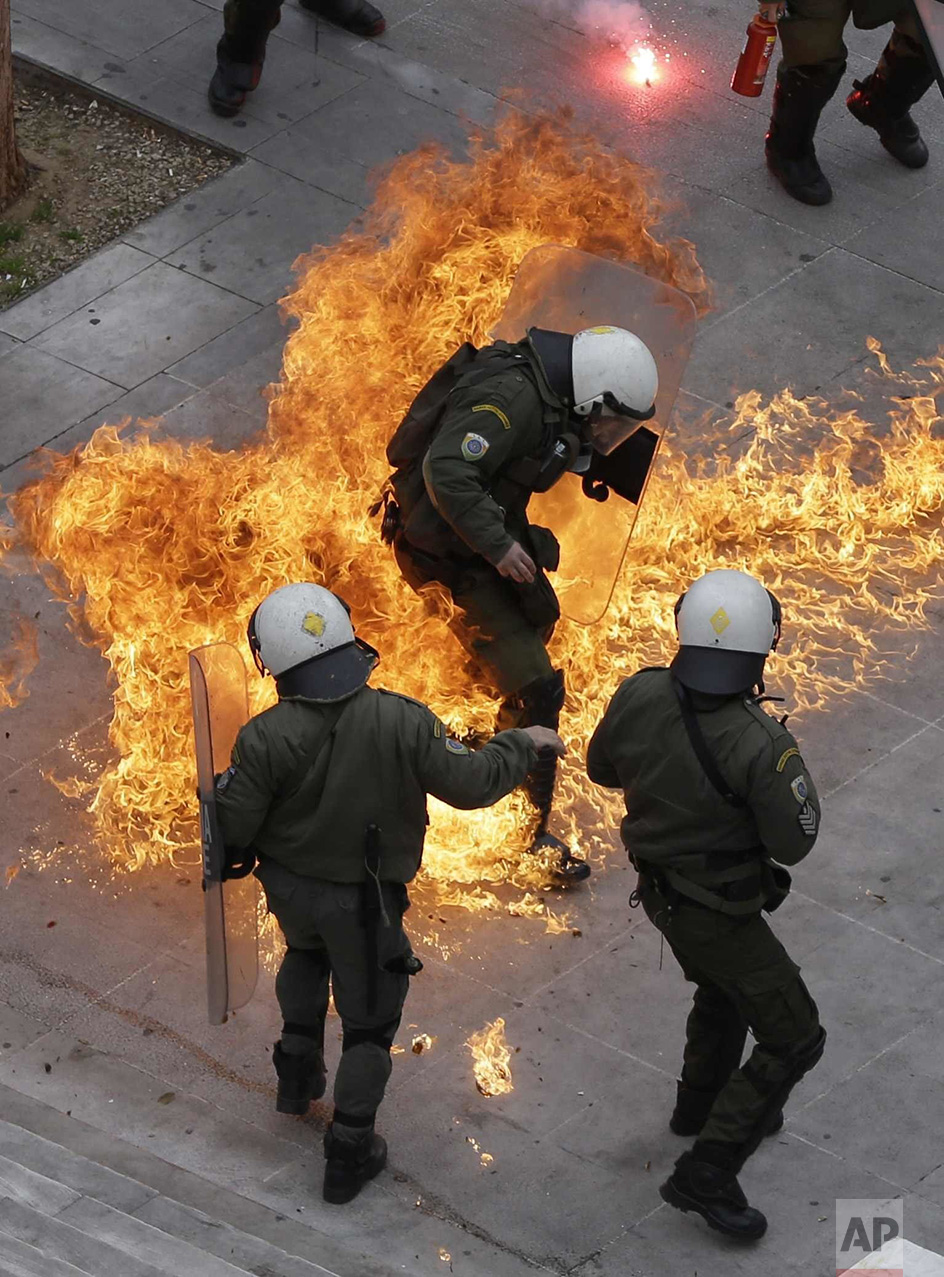 In this Thursday, Feb. 4, 2016 photo, riot policemen try to avoid a petrol bomb thrown by protesters during a 24-hour nationwide general strike in Athens. Clashes have broken out between Greek police and youths throwing fire bombs and stones, as tens of thousands of people march through central Athens to protest planned pension reforms. (AP Photo/Thanassis Stavrakis)