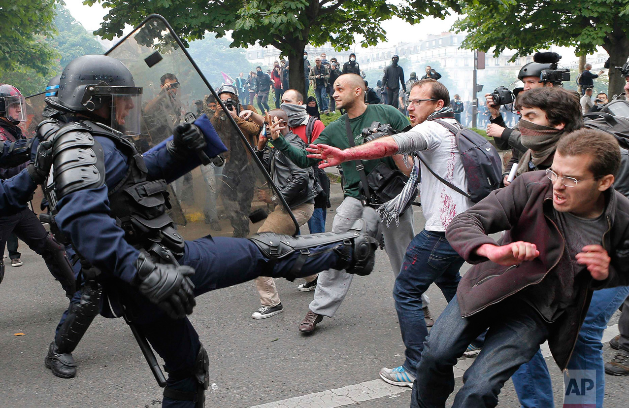 In this Thursday, May 26, 2016 photo, riot police officers clash with protestors during a demonstration held as part of nationwide labor actions in Paris, France. (AP Photo/Francois Mori)