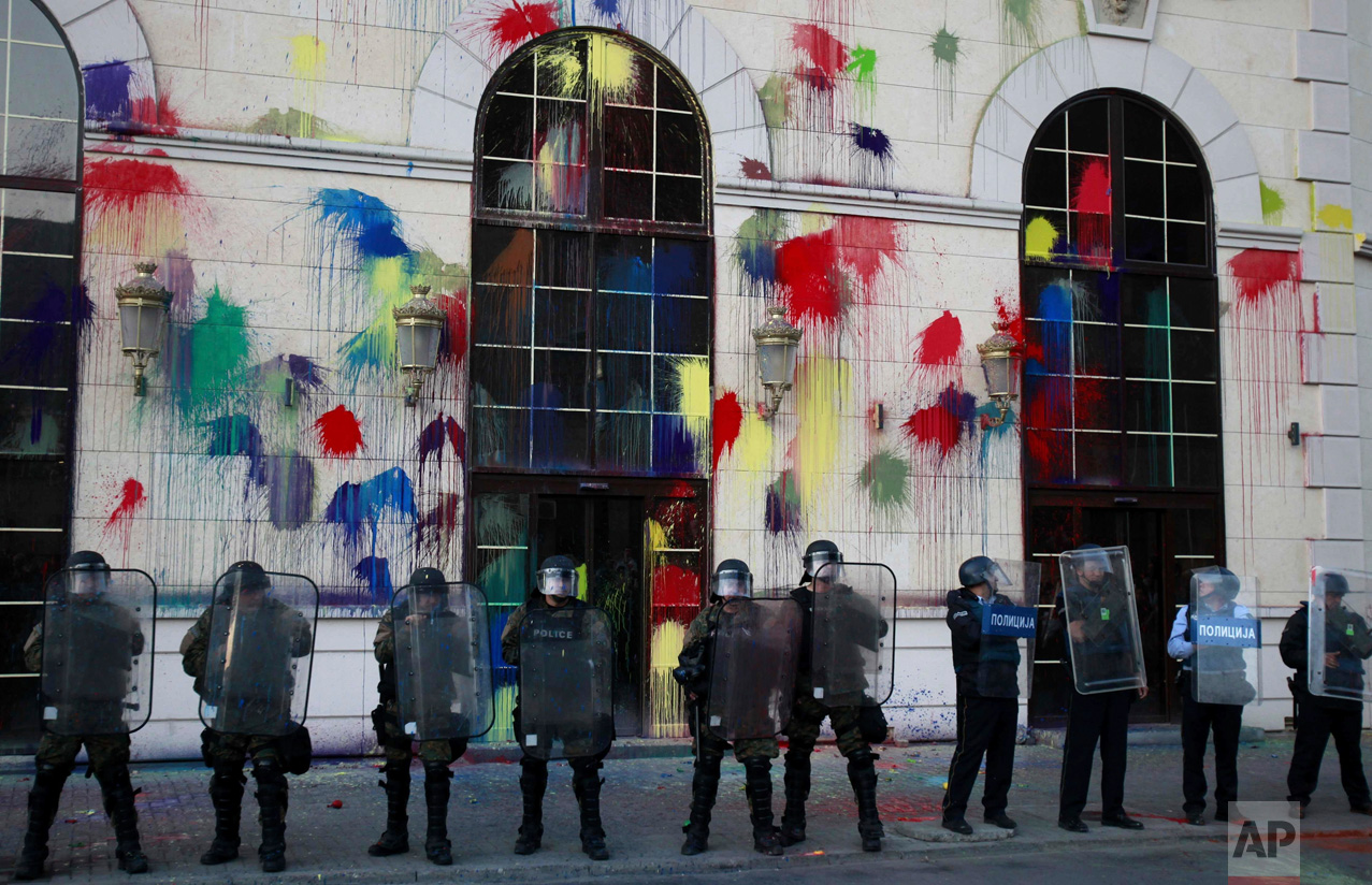 In this Friday, April 22, 2016 photo, police officers hold their shields as protestors pelt the new building of the Agency for Media Services with colored paint, during a protest in Skopje, Macedonia. Thousands of people have been protesting almost nightly in the Macedonian capital, Skopje, since President Gjorge Ivanov announced a decision last week to grant presidential pardons that halted criminal proceedings against dozens of people, including high-ranking politicians, accused in a wiretapping scandal that has roiled Macedonia for months. (AP Photo/Boris Grdanoski)
