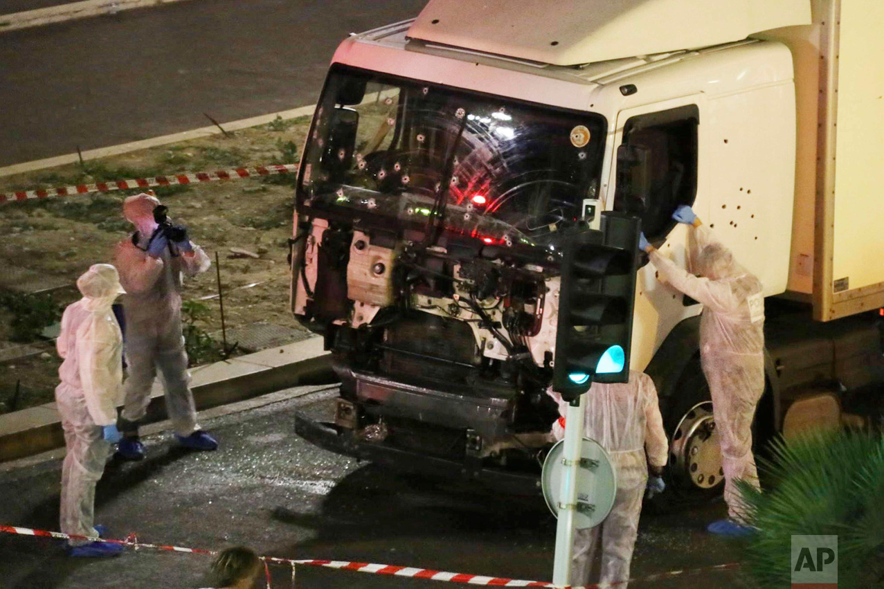 Authorities investigate a truck after it plowed through Bastille Day revelers in the French resort city of Nice, France, on July 14, 2016. France was ravaged by its third attack in two years when a large white truck mowed through revelers gathered for Bastille Day fireworks in Nice, killing dozens of people as it bore down on the crowd for more than a mile along the Riviera city's famed seaside promenade. (Sasha Goldsmith via AP)