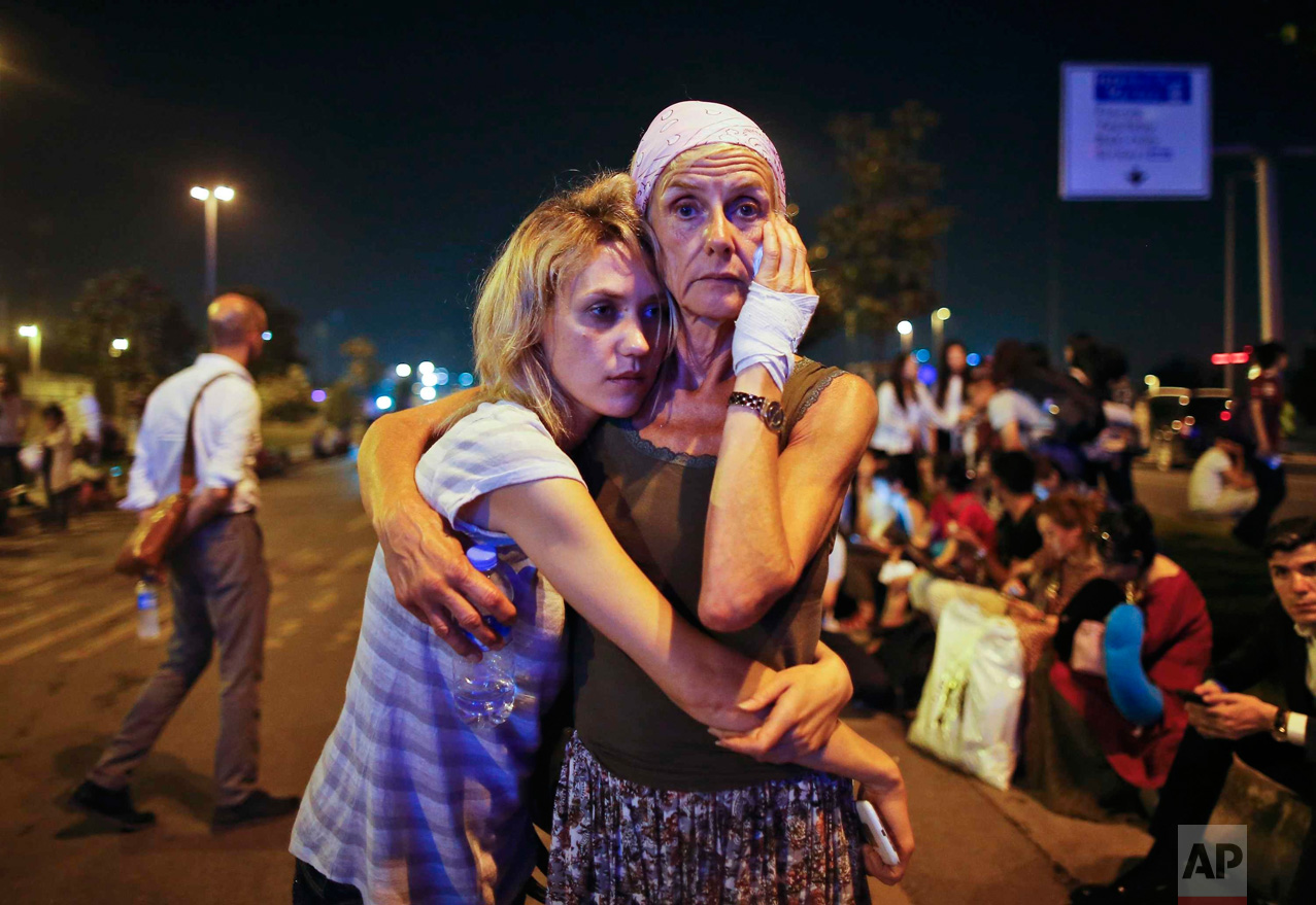 Passengers embrace each other as they wait outside Istanbul's Ataturk airport, on June 29, 2016, following their evacuation after a blast. Suspected Islamic State group extremists hit the international terminal of Istanbul's Ataturk airport, killing dozens of people and wounding many others. (AP Photo/Emrah Gurel)