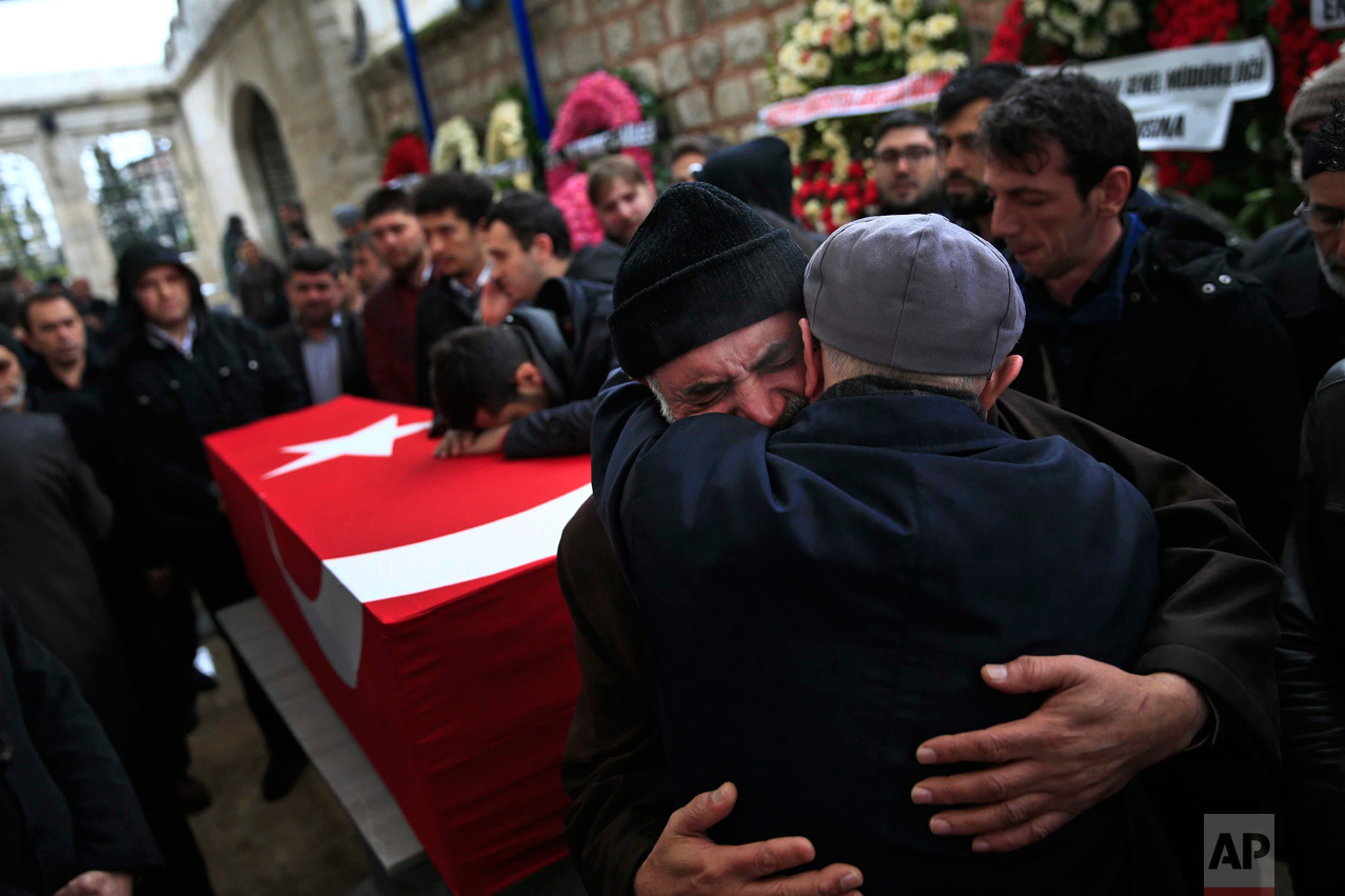 In this Tuesday, March 15, 2016 photo, Mustafa Alan, centre, the father of Mehmet Alan, 29, killed at Sunday's explosion in Ankara, embraces a mourner next to his son's coffin, during the funeral procession at Fatih Mosque n Istanbul. The blast which killed dozens of people and wounded scores of others, was the second deadly attack blamed on Kurdish militants in the capital in the past month. (AP Photo/Lefteris Pitarakis)