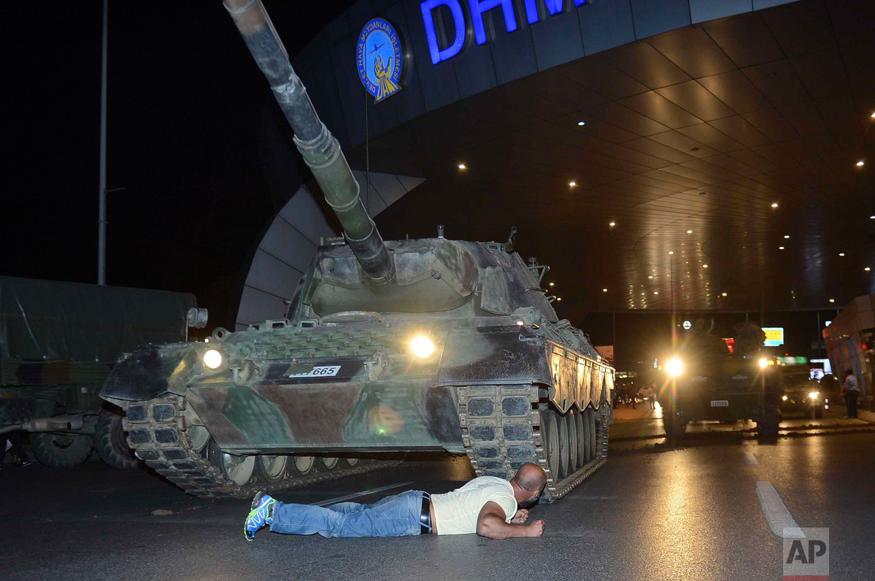 In this Saturday, July 16, 2016 photo, a man lays in front of a tank in the entrance to Istanbul's Ataturk airport. Members of Turkey's armed forces said they had taken control of the country, but Turkish officials said the coup attempt had been repelled early Saturday morning in a night of violence that left several people dead, according to state-run media. (Ismail Coskun/IHA via AP)