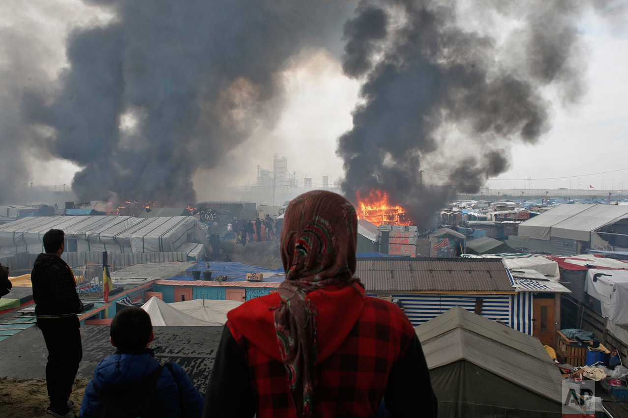 "In this Wednesday, Oct. 26, 2016 photo, people stand on a hill as smoke and flames rise from amidst the tents, after fires were started in the makeshift migrant camp known as ""the jungle"" near Calais, northern France. Firefighters have doused several dozen fires set by migrants as they left the makeshift camp where they have been living near the northern French city of Calais. (AP Photo/Thibault Camus)"