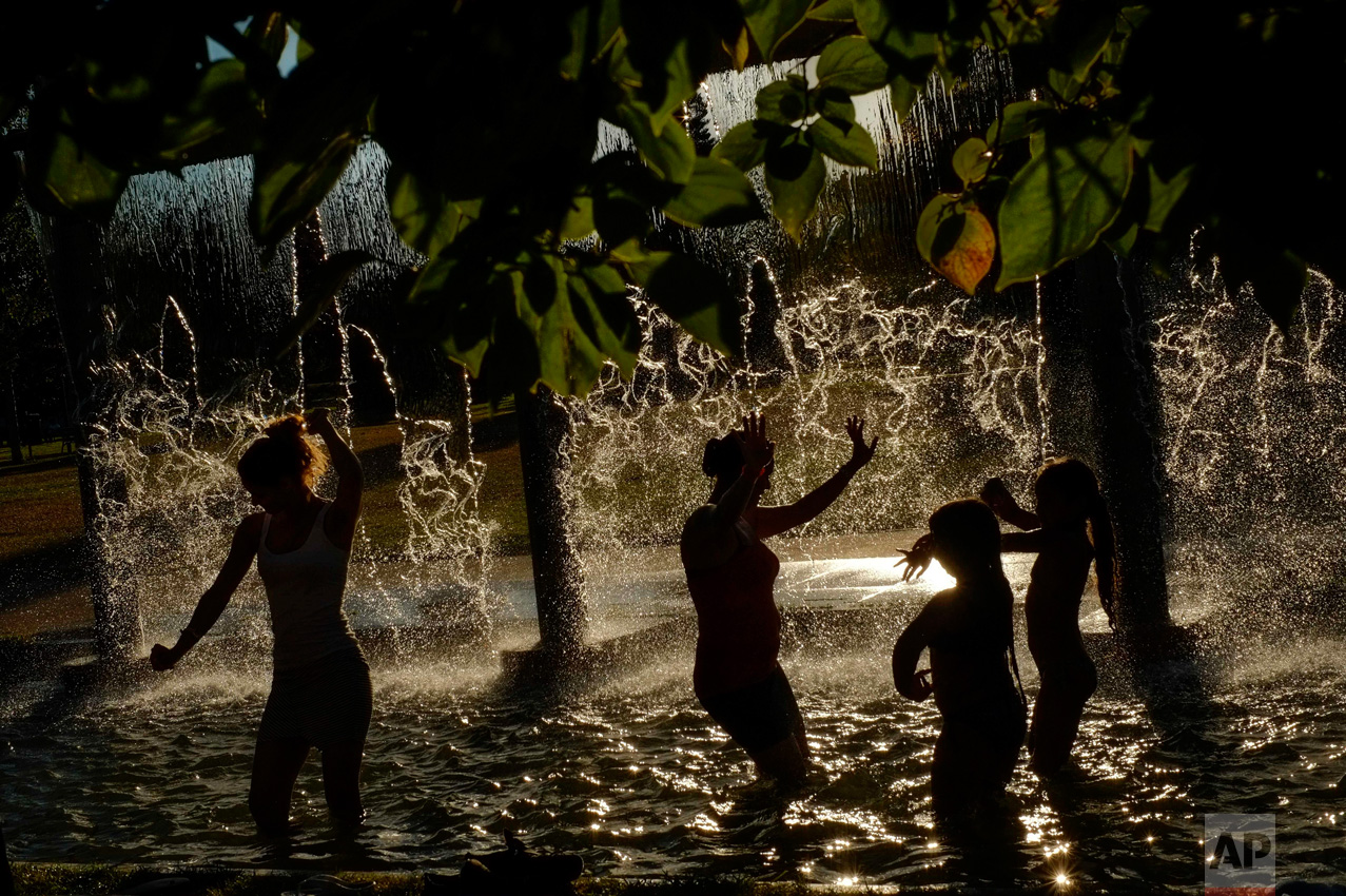 In this Wednesday, Aug. 24, 2016 photo, people cool off under a water fountain on a sunny day, in Pamplona northern Spain. The recent hot weather has prompted many people to cool off in the water fountains. (AP Photo/Alvaro Barrientos)