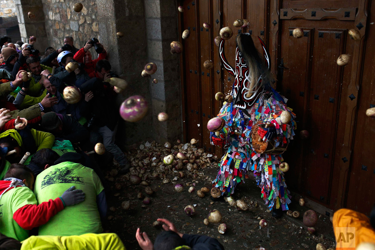 In this Wednesday, Jan. 20, 2016 photo, people throw turnips at the Jarramplas as he makes his way through the streets beating his drum during the Jarramplas festival in Piornal, Spain. (AP Photo/Francisco Seco)