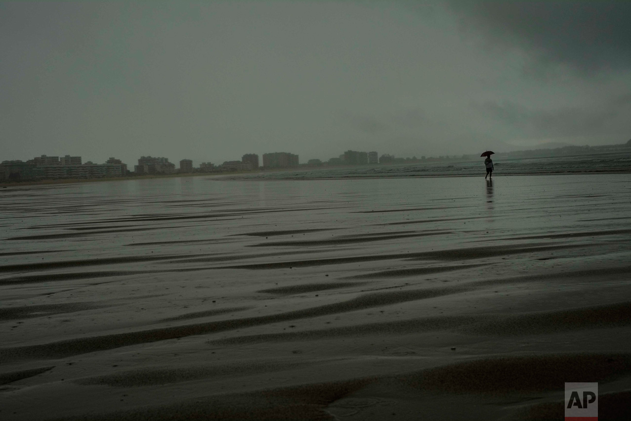 In this Saturday, July 30, 2016 photo, a man shelters from the rain with an umbrella as he goes for a walk on the seaside during a rainier summer day, in Laredo, northern Spain. (AP Photo/Alvaro Barrientos)