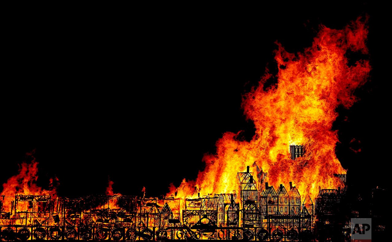In this Sunday, Sept. 4, 2016 photo, a 120-metre long sculpture of the 17th-century London skyline is set alight in a retelling of the story of the Great Fire of London in 1666, in London. The event was part of a collaboration between American 'burn' artist David Best and Artichoke, commemorating the Great Fire of London in 1666. (AP Photo/Frank Augstein)