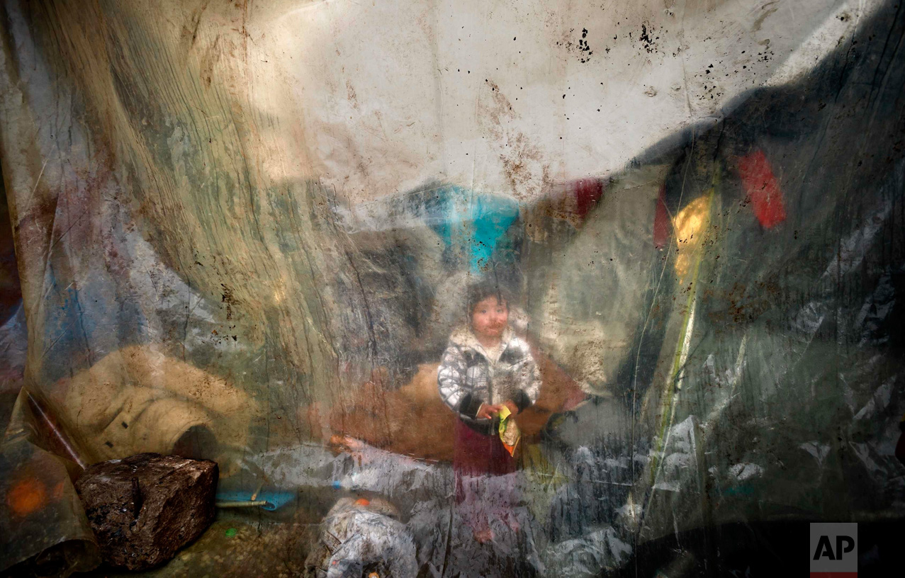 In this Tuesday, March 15, 2016 photo, a migrant child sits behind plastic sheets covering tents during a rainfall in a makeshift camp at the northern Greek border post of Idomeni, Greece. (AP Photo/Vadim Ghirda)