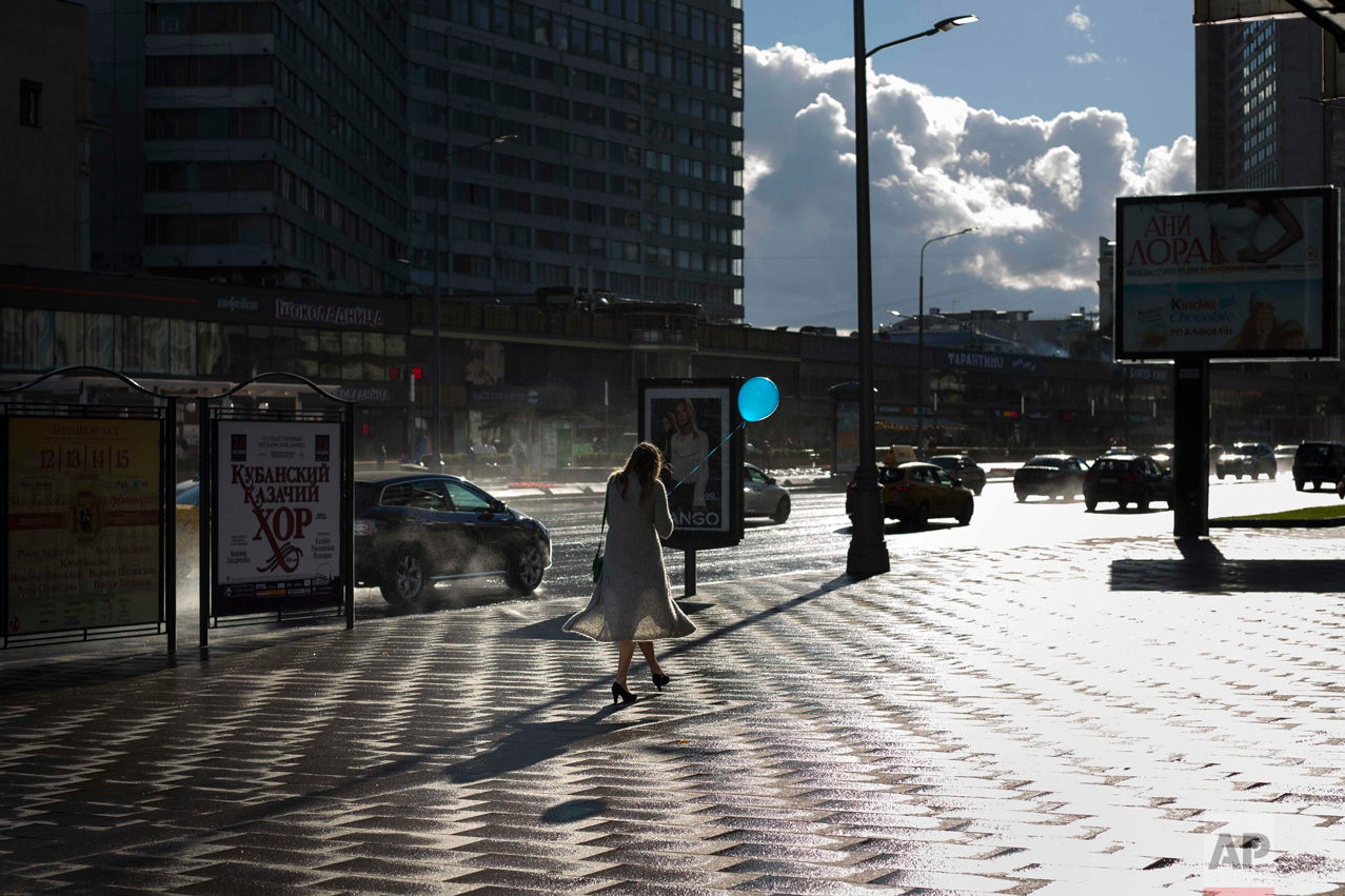In this Thursday, Sept. 8, 2016 photo, a pedestrian holds a balloon after a rain in Moscow, Russia. (AP Photo/Alexander Zemlianichenko)
