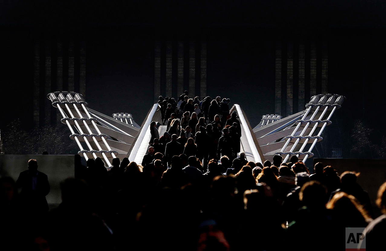 In this Tuesday, Feb. 16, 2016 photo, pedestrians stroll over the Millennium Bridge in London. Temperatures dropped below zero overnight and daytime showed a clear blue sky with bright sunshine. (AP Photo/Frank Augstein)