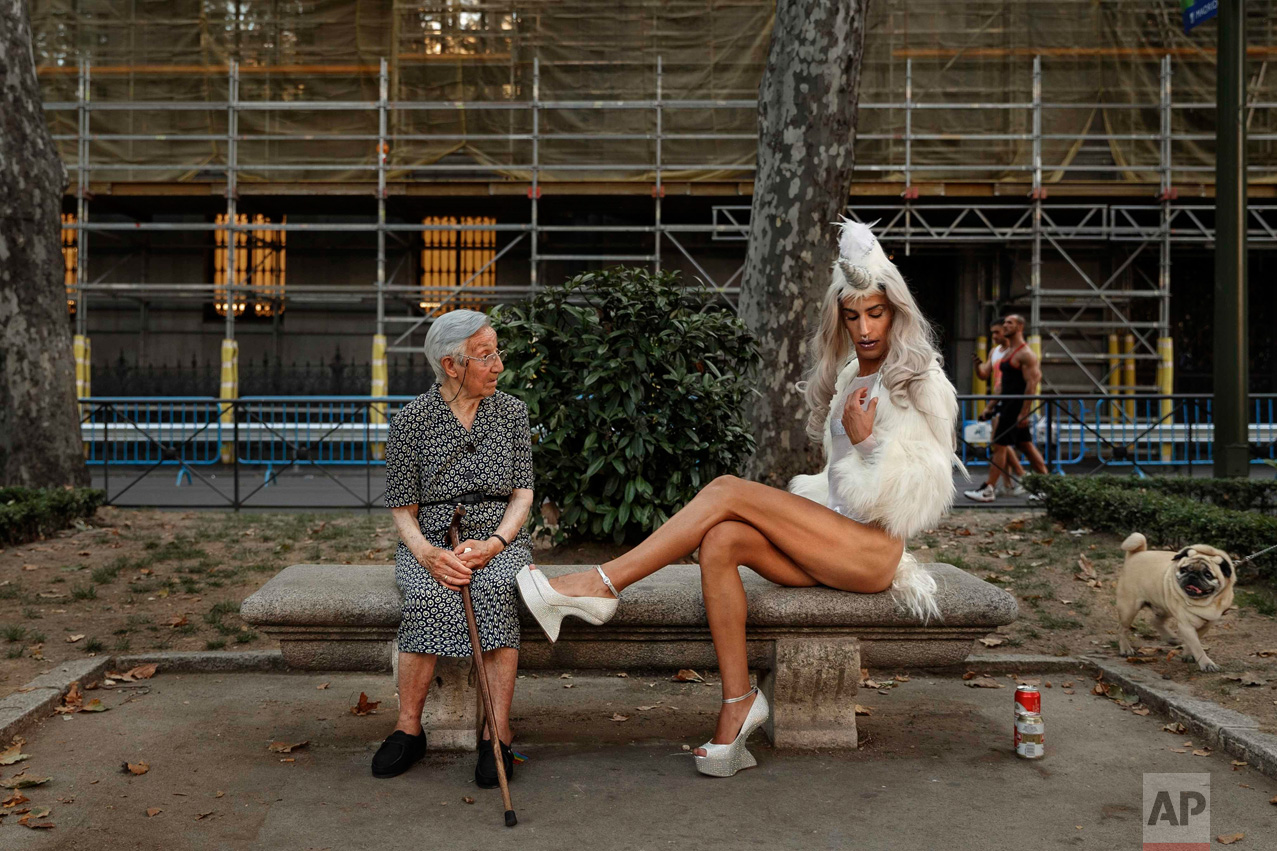 In this Saturday, July 2, 2016 photo, a woman looks across as a gay parade participant poses for pictures during Gay Pride parade in Madrid, Spain. (AP Photo/Daniel Ochoa de Olza)