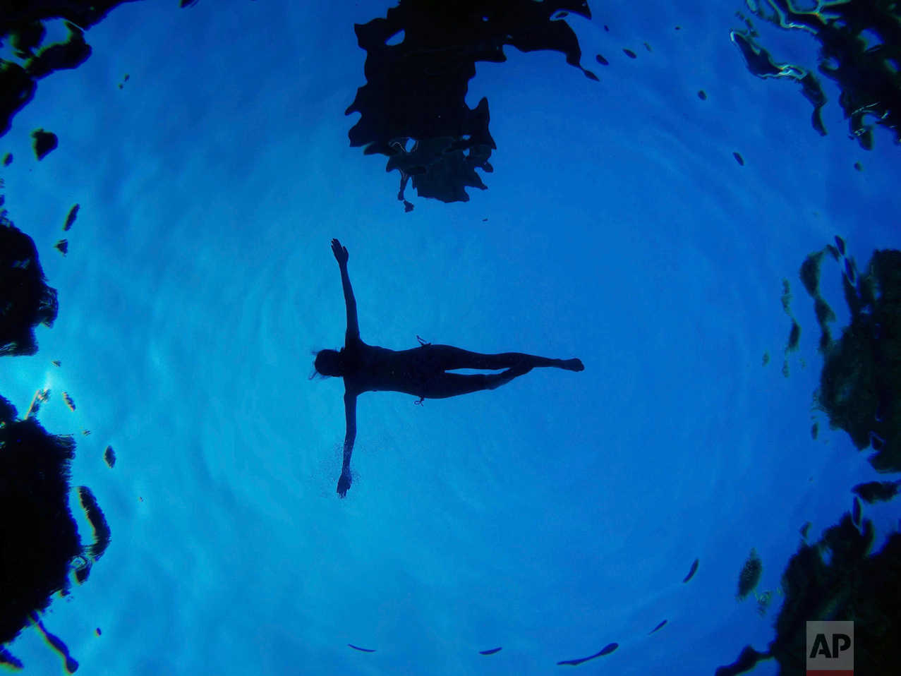 A Sunday, Aug. 28, 2016 photo taken underwater of a woman floating in a swimming pool during a summer day in Madrid, Spain. (AP Photo/Daniel Ochoa de Olza)
