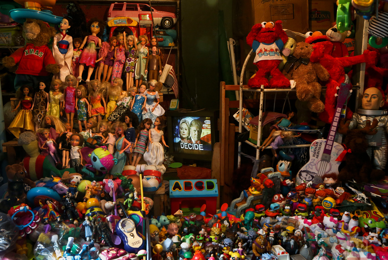 In this Nov. 8, 2016 photo, U.S. presidential Democratic nominee Hillary Clinton, and Republican nominee Donald Trump, are seen on a television screen in a Nicaraguan newscast surrounded by secondhand toys and puppets at the popular market in Managua, Nicaragua. Trump was elected the 45th President of the United States, marking the end of an unusually bitter presidential campaign. (AP Photo/Esteban Felix)
