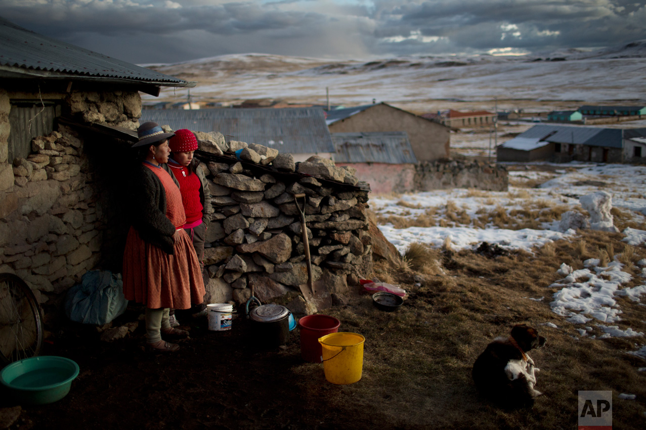 In this July 9, 2016 photo, Rosa Carcabusto, 29, and her daughter Maria Luque, 13, stand outside their house before preparing a soup of wheat and dissected potatoes for dinner in San Antonio de Putina, in Puno's region, Peru. In the villages located almost 5000 meters above sea level, temperatures drop to -20 degrees during the winter season, producing snow and the death of thousands of alpacas and sheep, which are the only livelihood among indigenous peasants in the region of Puno, southeastern Peru. (AP Photo/Rodrigo Abd)