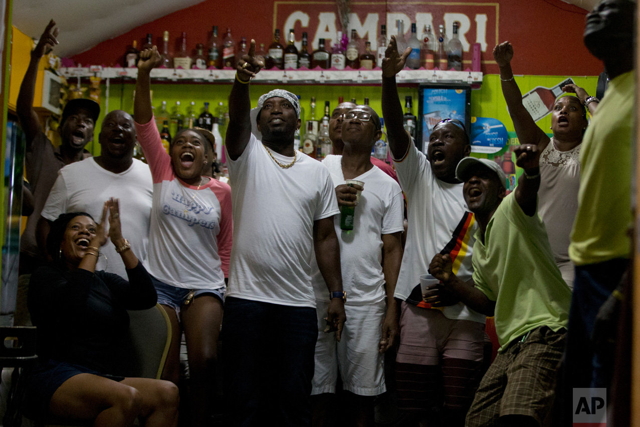 In this Aug. 14, 2016 photo, patrons watch Jamaica's Usain Bolt winning the Rio Olympics men's 100m final in Gros Islet, St. Lucia. (AP Photo/Ricardo Mazalan)