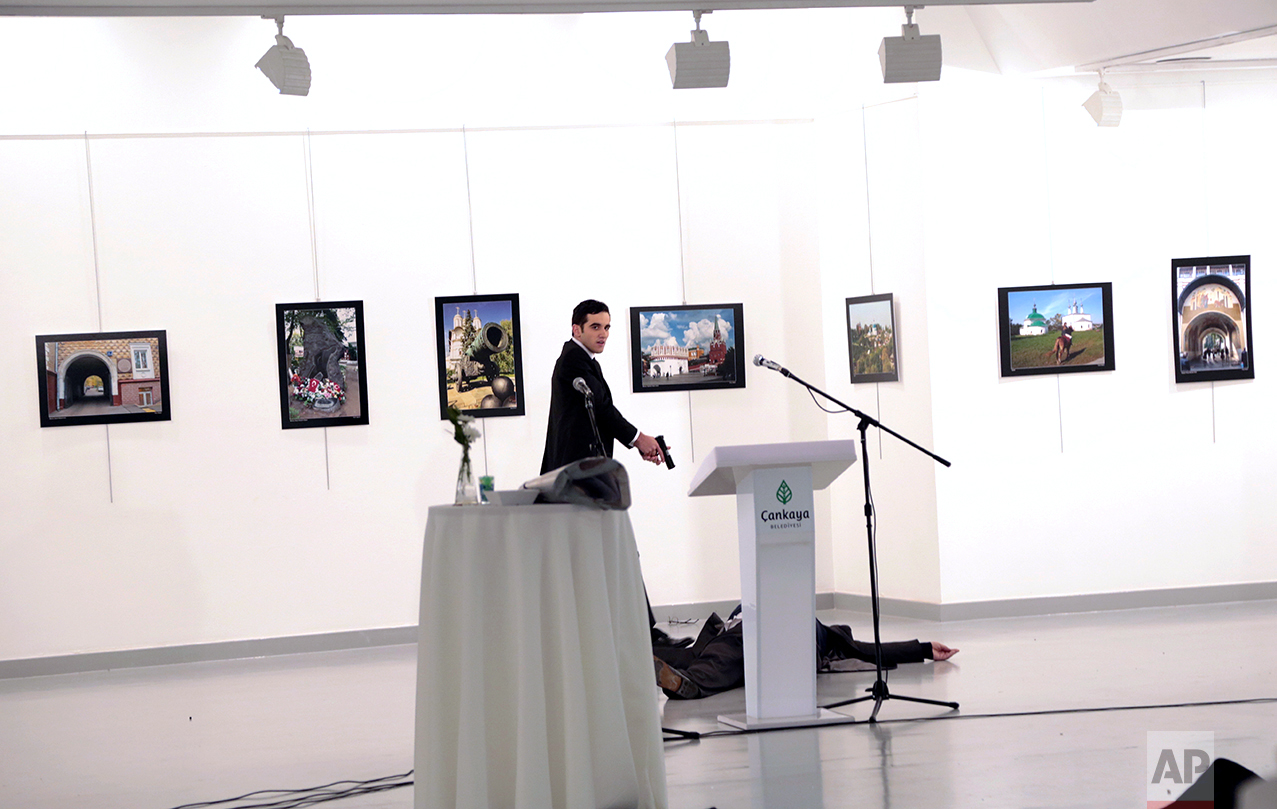 A man identified as Mevlut Mert Altintas shouts after shooting the Russian Ambassador to Turkey, Andrei Karlov, at a photo gallery in Ankara, Turkey, Monday, Dec. 19, 2016. (AP Photo/Burhan Ozbilici)