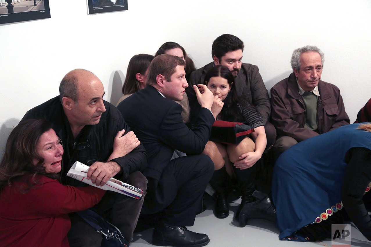 People crouch in a corner after Andrei Karlov, the Russian Ambassador to Turkey, was shot at a photo gallery in Ankara, Turkey, Monday, Dec. 19, 2016. Karlov, 62, was several minutes into a speech at an embassy-sponsored photo exhibition when a man fired a gun at him. Karlov was rushed to a hospital after the attack and later died from his gunshot wounds. (AP Photo/Burhan Ozbilici)
