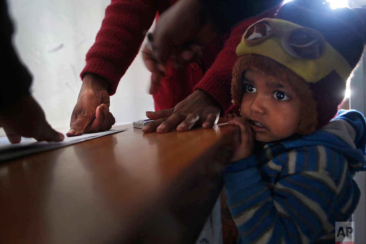 """In this photo taken on Monday, Dec 19, 2016, Saro Kumari Mandal, 26, gives her thumb impression to receive compensation after her husband died as a migrant worker in Qatar, as her son stands by her side at the Department of Foreign Employment in Kathmandu, Nepal. Saro received $2,777 from the Foreign Employment Promotion Board. She said she would use the money to open a small store in the village selling cookies and noodles, and also invest in a sewing machine. She wants to earn money for their son's education. """"I want to make my son a teacher or a doctor when he grows up,"""" she said. (AP Photo/Niranjan Shrestha)"""
