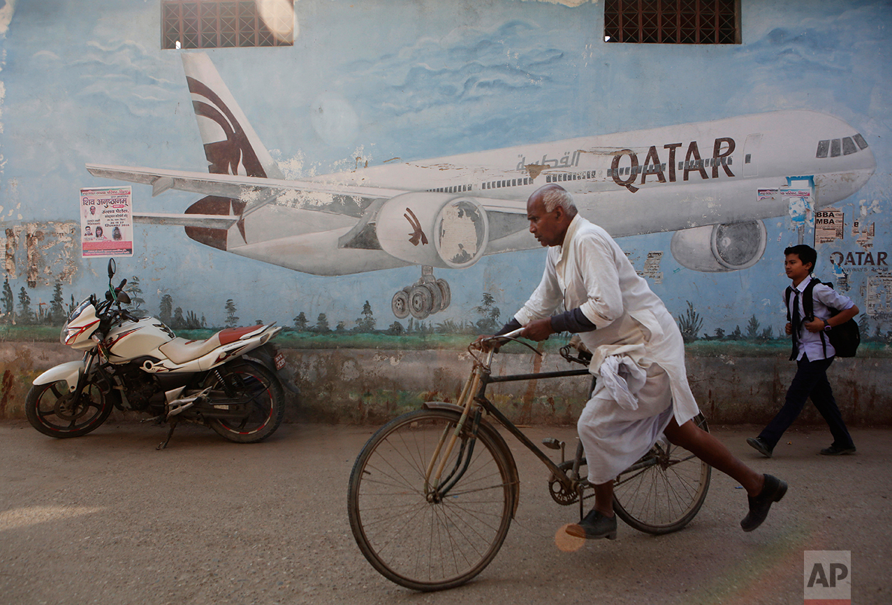 In this photo taken on Monday, Nov. 30, 2016, a Nepalese man rides his bicycle in front of an advertisement of Qatar airways painted on a wall in Janakpur district, Nepal. The number of Nepali workers going abroad has more than doubled since the country began promoting foreign labor in recent years: from about 220,000 in 2008 to about 500,000 in 2015. The unskilled workers fill a host of global demands: building highways, stadiums and houses in Gulf states and guarding shopping malls, sewing sweatshirts and assembling televisions in Malaysia. (AP Photo/Niranjan Shrestha)