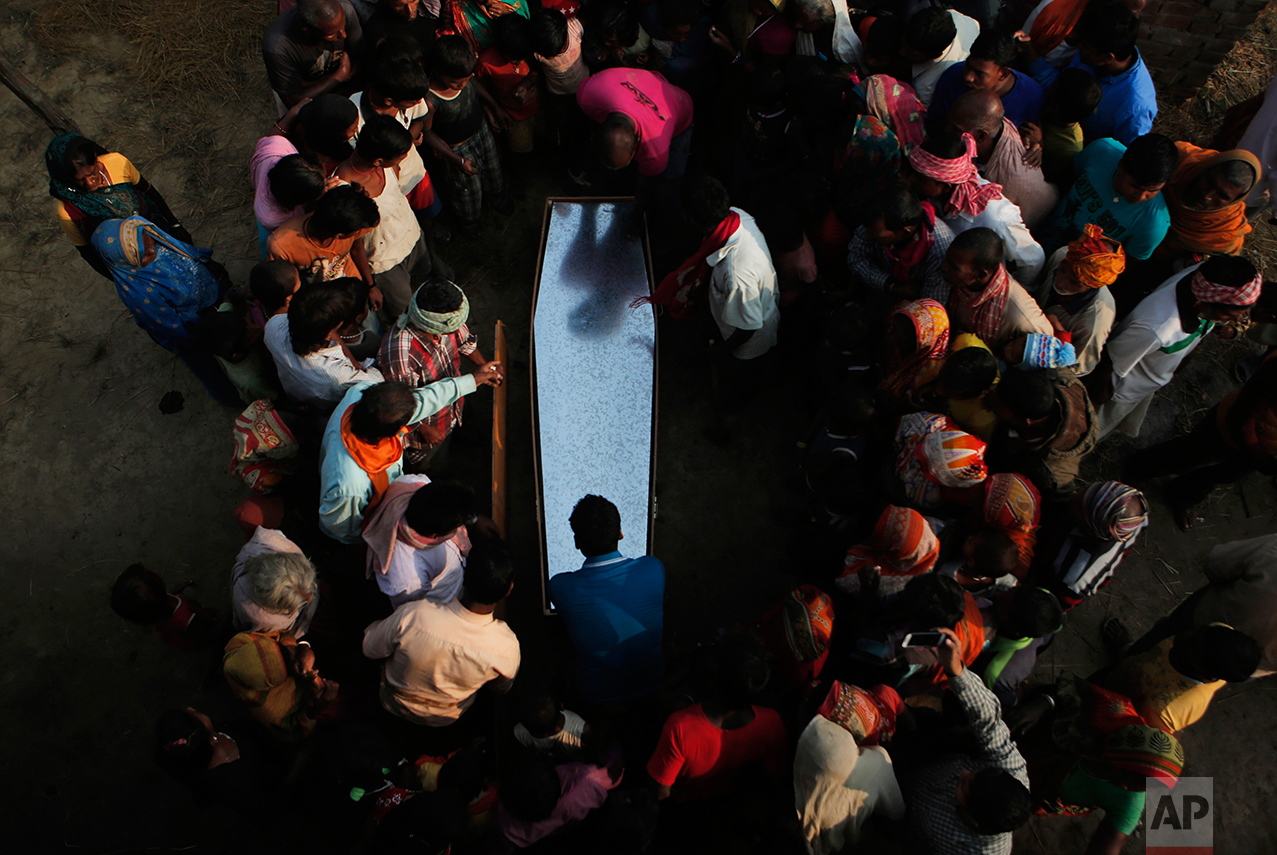 In this Nov. 23, 2016 photo, relatives and villagers gather around the coffin of Balkisun Mandal Khatwe at Belhi village, Saptari district of Nepal. Balkisun, who had been working for Habtoor Leighton Group in Qatar for less than a month, died in his sleep. The number of Nepali workers going abroad has more than doubled since the country began promoting foreign labor in recent years: from about 220,000 in 2008 to about 500,000 in 2015. Yet the number of deaths among those workers has risen much faster in the same period. In total, over 5,000 workers from this small country have died working abroad since 2008, more than the number of U.S. troops killed in the Iraq War. (AP Photo/Niranjan Shrestha)
