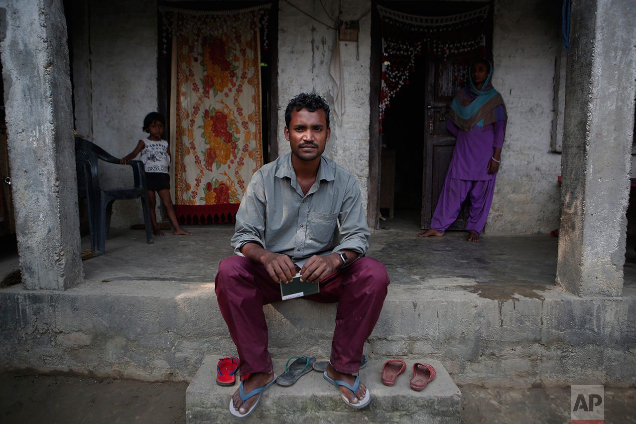 """In this Nov. 23, 2016 photo, Mohammed Tohit, 28, holds his passport in front of the solid, cement and plaster home that he built for his family in Belhi Village, Nepal. Tohit is the envy and inspiration of the village. He worked in Malaysia for almost six years sewing clothes for Nike, Lacoste and Columbia Sportswear, saving more than $20,000, enough to build the sturdy two-bedroom house. """"I am scared, sure, but I have no way to earn anything here,"""" he says. """"I have no choice but to leave again."""" (AP Photo/Niranjan Shrestha)"""