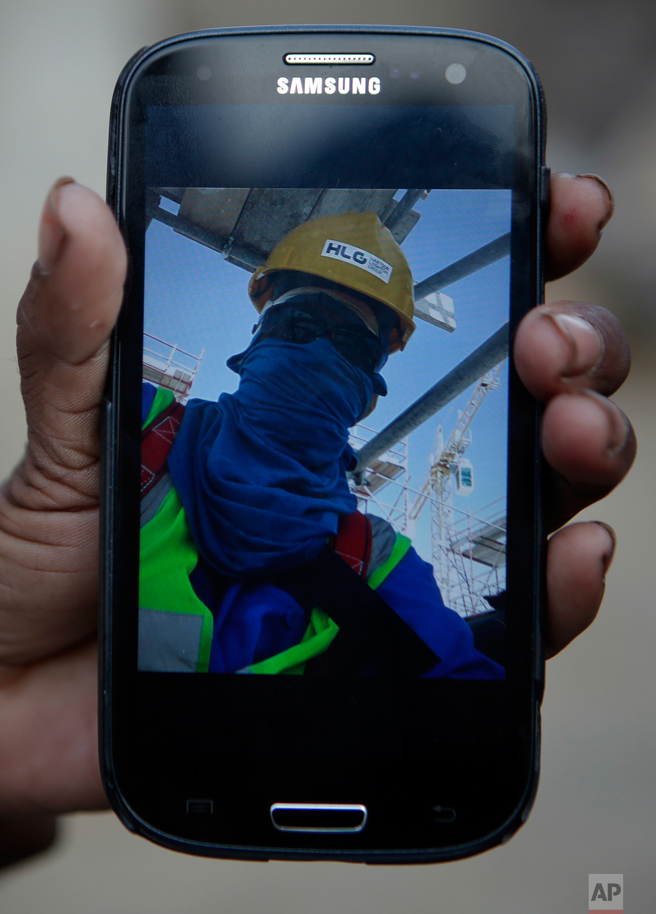 """In this Wednesday, Nov. 30, 2016, Saro Kumari Mandal, 26, holds a mobile phone displaying a selfie her husband Balkisun Mandal Khatwe had taken in Qatar in his yellow work hardhat and protective sunglasses, at her village in Belhi, Saptari District of Nepal. Saro had chatted with Balkisun through Facebook Messenger just the evening before his death. This is what happened, according to his supervisor: """"After work he went to dinner at 7 and bed at 10. In the morning we tried to wake him up but he didn't respond. We took the body to the hospital where they did an autopsy and said it was cardiac arrest."""" About 10 percent of Nepal's 28 million residents are working abroad. They send back more than $6 billion a year, amounting to about 30 percent of the country's annual revenues. Only Tajikistan and Kyrgyzstan are more dependent on foreign earnings. (AP Photo/Niranjan Shrestha)"""