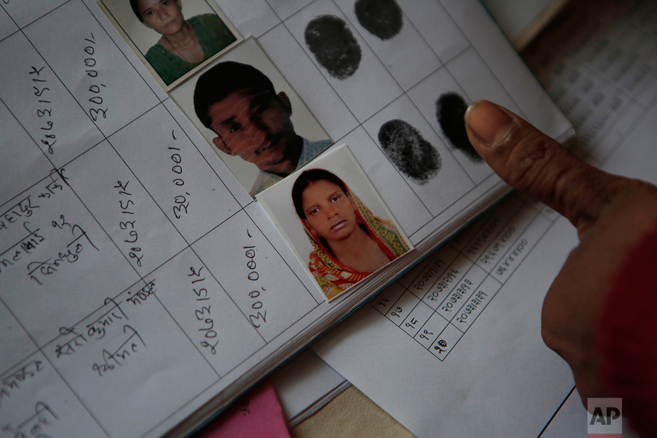 """In this Tuesday, Dec 20, 2016 photo, Saro Kumari Mandal, 26, gives her fingerprint to receive compensation from the Foreign Employment Promotion Board after her husband died as a migrant worker in Qatar, in Kathmandu, Nepal. She received $2,777 which she said she would use to open a small store in the village selling cookies and noodles, and also invest in a sewing machine. She wants to earn money for their son's education. """"I want to make my son a teacher or a doctor when he grows up,"""" she said. (AP Photo/Niranjan Shrestha)"""
