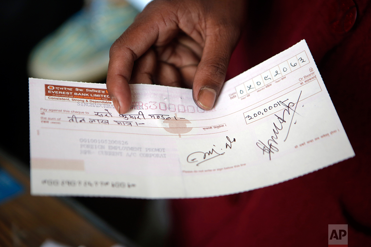 """In this Tuesday, Dec 20, 2016 photo, Saro Kumari Mandal, 26, holds a cheque received as compensation from the Foreign Employment Promotion Board after her husband died as a migrant worker in Qatar, in Kathmandu, Nepal. She received $2,777 which she said she would use to open a small store in the village selling cookies and noodles, and also invest in a sewing machine. She wants to earn money for their son's education. """"I want to make my son a teacher or a doctor when he grows up,"""" she said. (AP Photo/Niranjan Shrestha)"""