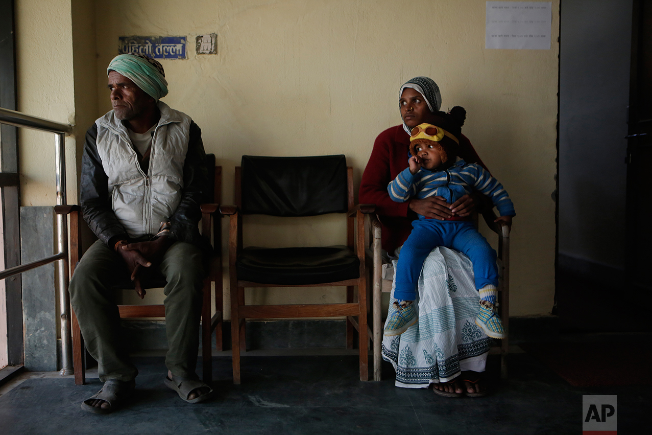 """In this photo taken on Monday, Dec 19, 2016, Saro Kumari Mandal, 26, sits with her son and her father-in-law at the Department of Foreign Employment to receive compensation after her husband died as a migrant worker in Qatar, in Kathmandu, Nepal. Eventually, with help, she received $2,777 from the Foreign Employment Promotion Board. She said she would use the money to open a small store in the village selling cookies and noodles, and also invest in a sewing machine. She wants to earn money for their son's education. """"I want to make my son a teacher or a doctor when he grows up,"""" she said. (AP Photo/Niranjan Shrestha)"""