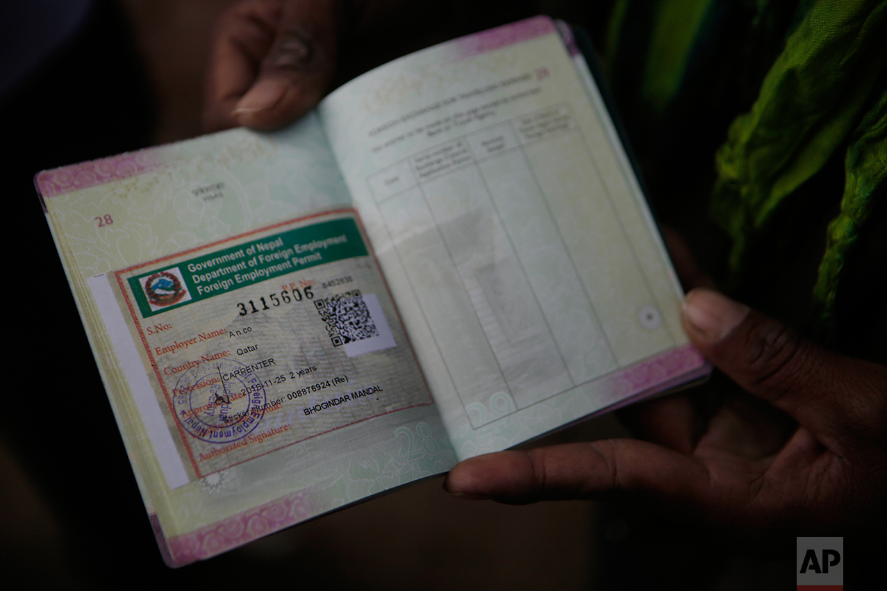 In this Nov 25, 2016 photo, a Nepalese man shows his passport with a working permit at the Department of Foreign Employment (DoFE) in Kathmandu, Nepal. The number of Nepali workers going abroad has more than doubled since the country began promoting foreign labor in recent years: from about 220,000 in 2008 to about 500,000 in 2015. The unskilled workers fill a host of global demands: building highways, stadiums and houses in Gulf states and guarding shopping malls, sewing sweatshirts and assembling televisions in Malaysia. (AP Photo/Niranjan Shrestha)