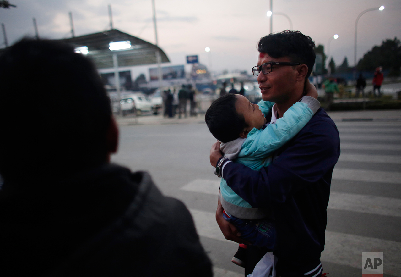 In this Monday, Nov. 28, 2016 photo, a Nepali migrant worker Krishna Bahadur Tamang, 32, carries his son before departing for Qatar at Tribhuwan Internation airport in Kathmandu, Nepal. The number of Nepali workers going abroad has more than doubled since the country began promoting foreign labor in recent years: from about 220,000 in 2008 to about 500,000 in 2015. Yet the number of deaths among those workers has risen much faster in the same period. In total, over 5,000 workers from this small country have died working abroad since 2008, more than the number of U.S. troops killed in the Iraq War. (AP Photo/Niranjan Shrestha)