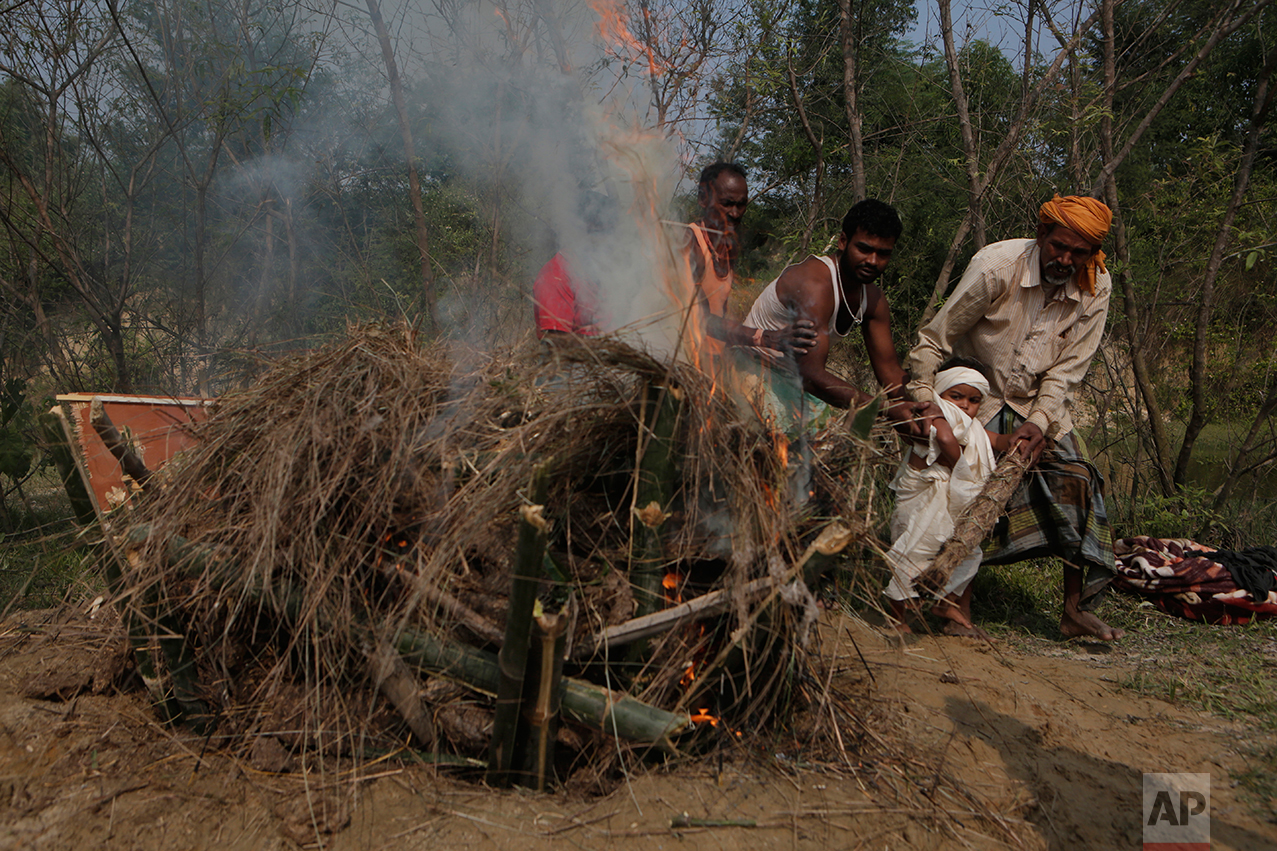 In this Wednesday, Nov. 23, 2016 photo, a priest helps Shivendra Kumar Mandal, 3, nicknamed Siban, perform cremation rituals before lighting the funeral pyre of his father Balkisun Mandal Khatwe, at Belhi village in Saptari district of Nepal. Balkisun died in his sleep in Qatar, where he was working Habtoor Leighton Group, loading trucks to build new highways. Nepal is one of the poorest and least developed countries in the world, and Belhi is one of its poorest places. The Mandals live eight people to a room in one of about 700 mud-and-stick homes set among dry, sparse rice paddies. (AP Photo/Niranjan Shrestha)