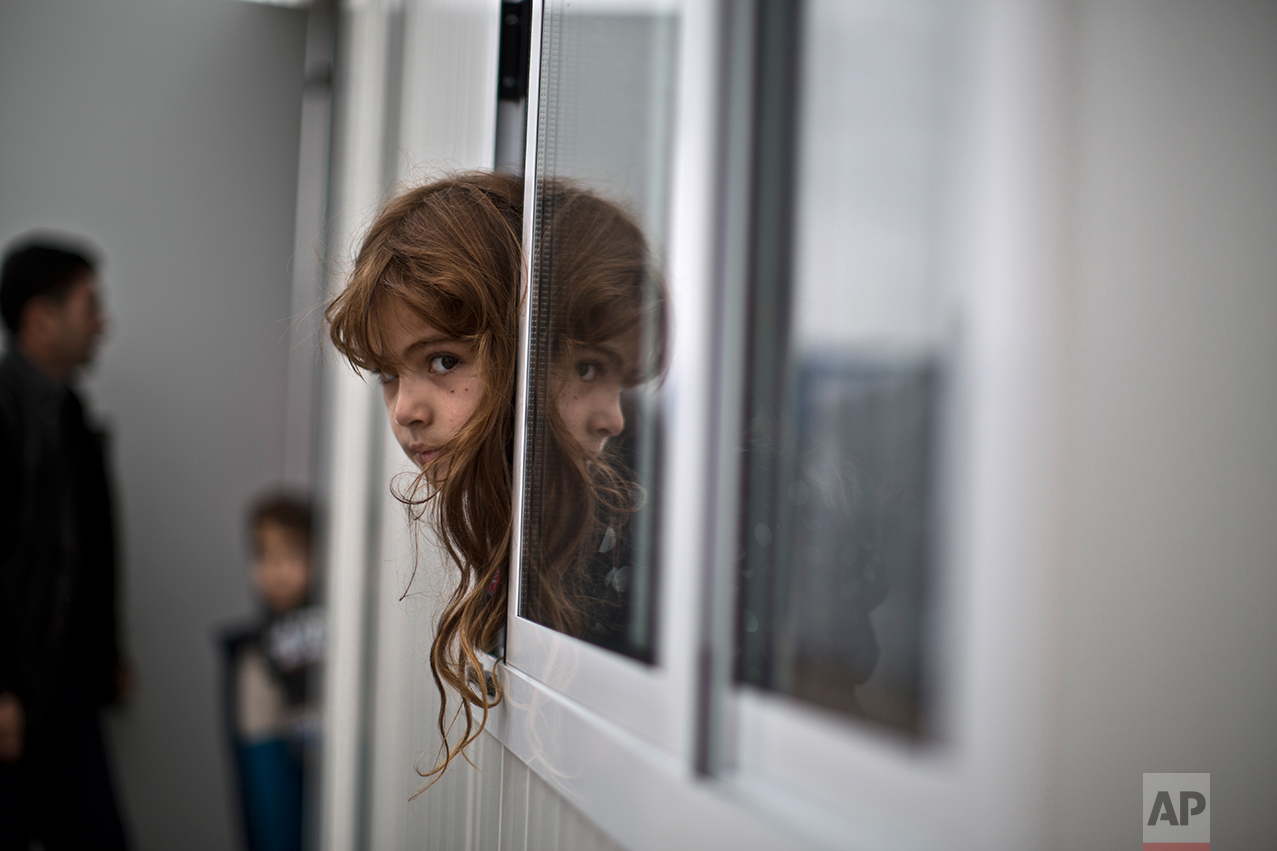 An Iraqi refugee girl looks outside her family's shelter at the refugee camp of Ritsona about 86 kilometers (53 miles) north of Athens, Wednesday, Dec. 28, 2016. (AP Photo/Muhammed Muheisen)