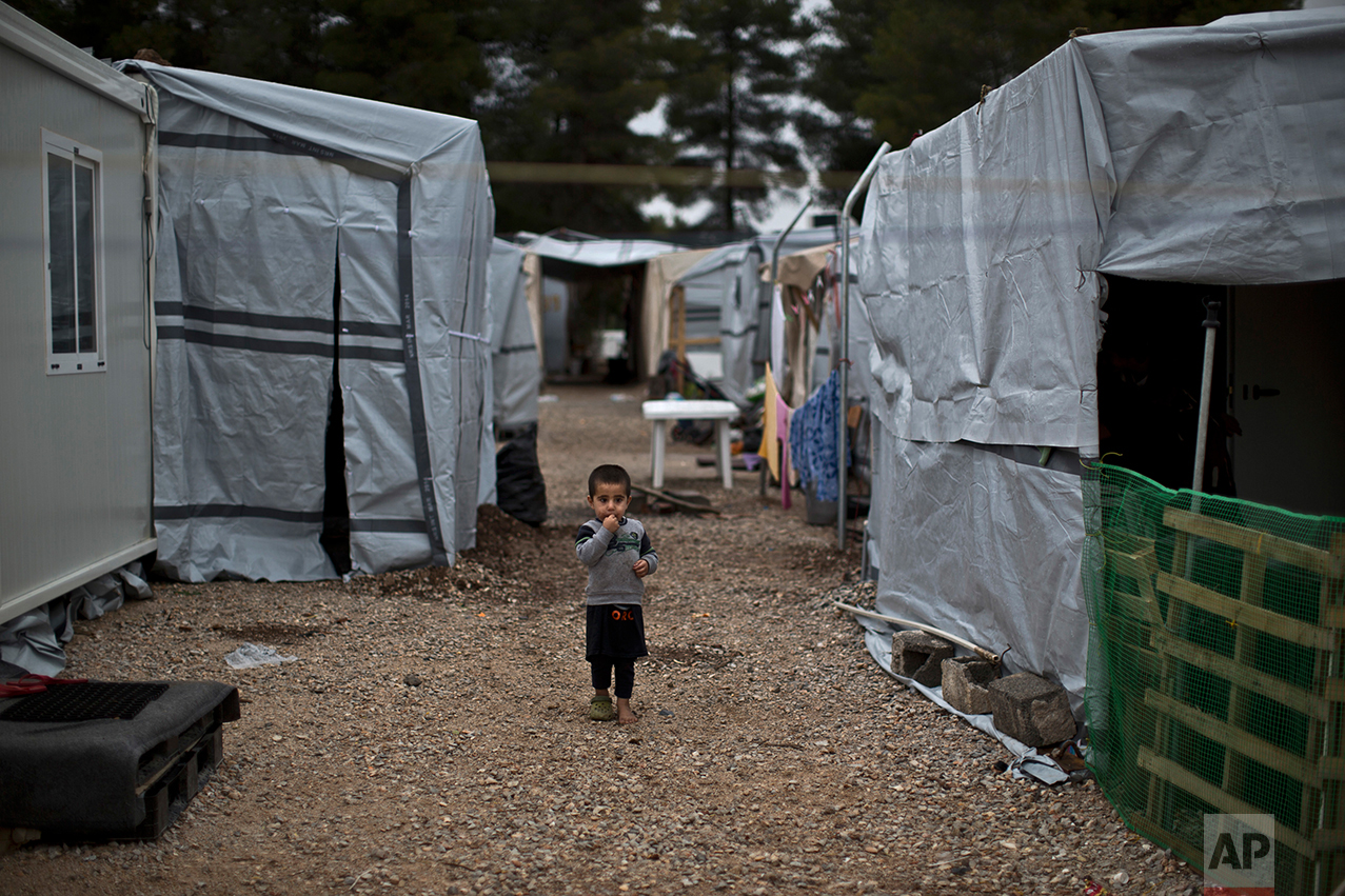 A Syrian refugee child walks between shelters at the refugee camp of Ritsona about 86 kilometers (53 miles) north of Athens, Wednesday, Dec. 28, 2016. (AP Photo/Muhammed Muheisen)