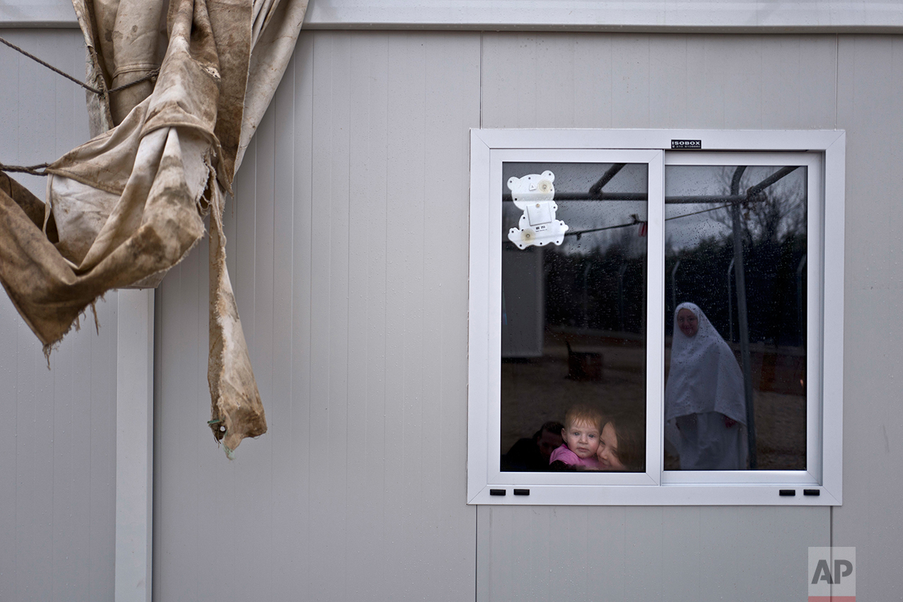 Syrian refugee Raneen Mahmoud, 5, and her younger sister Zainab, 6 months, look at their mother Randa, 30, from their shelter at the refugee camp of Ritsona about 86 kilometers (53 miles) north of Athens, Wednesday, Dec. 28, 2016. (AP Photo/Muhammed Muheisen)