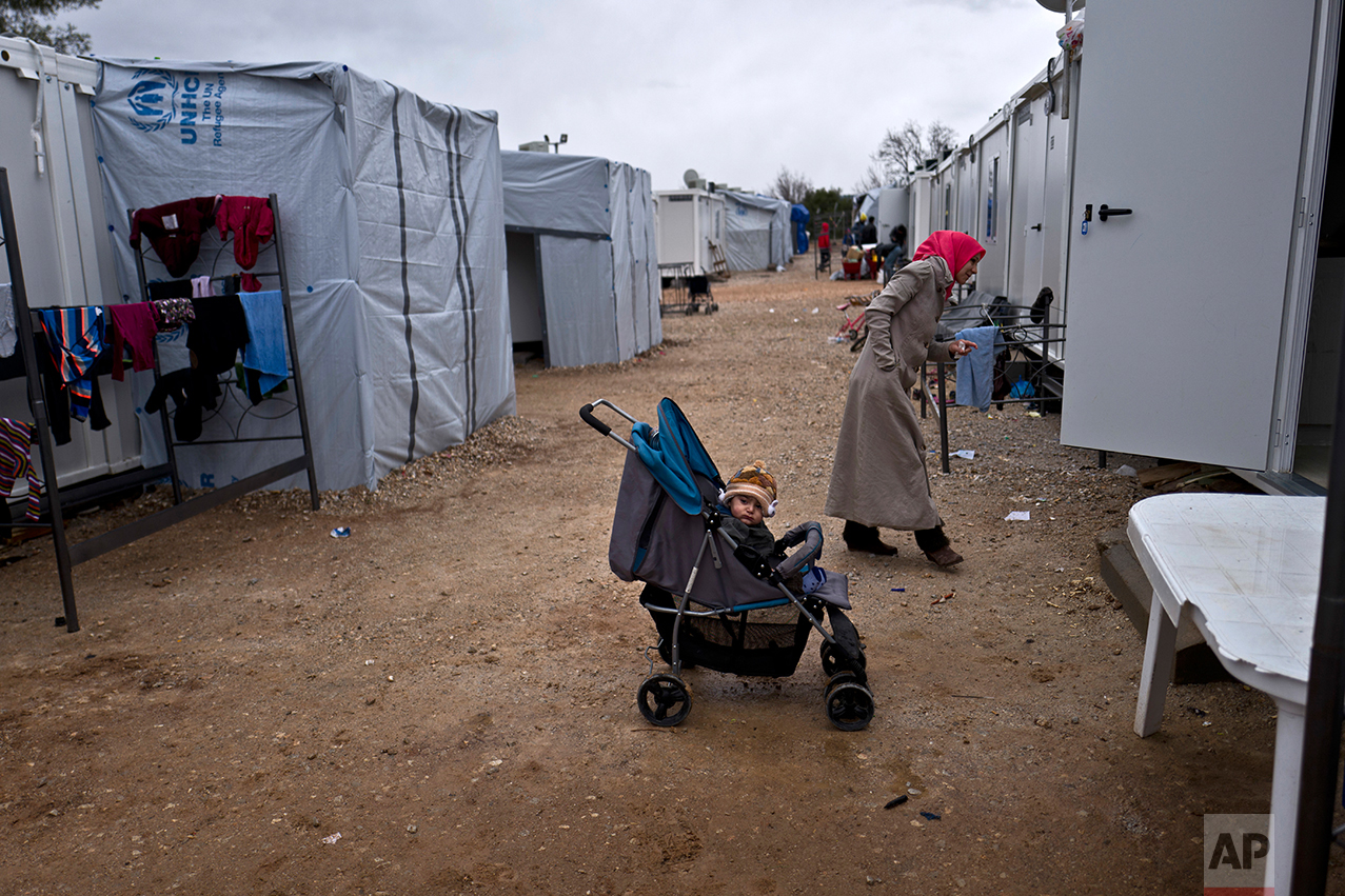 Syrian refugee child Alan Jouva, 2, sits in a stroller outside his family's shelter at the refugee camp of Ritsona about 86 kilometers (53 miles) north of Athens, Wednesday, Dec. 28, 2016. (AP Photo/Muhammed Muheisen)