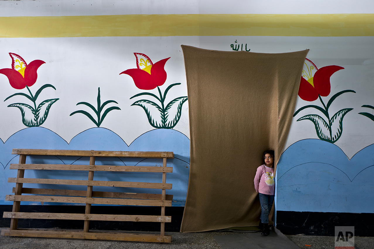 Tharwat, a 6-year-old Afghan refugee girl stands at the doorway of her family's shelter at the refugee camp of Oinofyta about 58 kilometers (36 miles) north of Athens, Tuesday, Dec. 27, 2016. (AP Photo/Muhammed Muheisen)