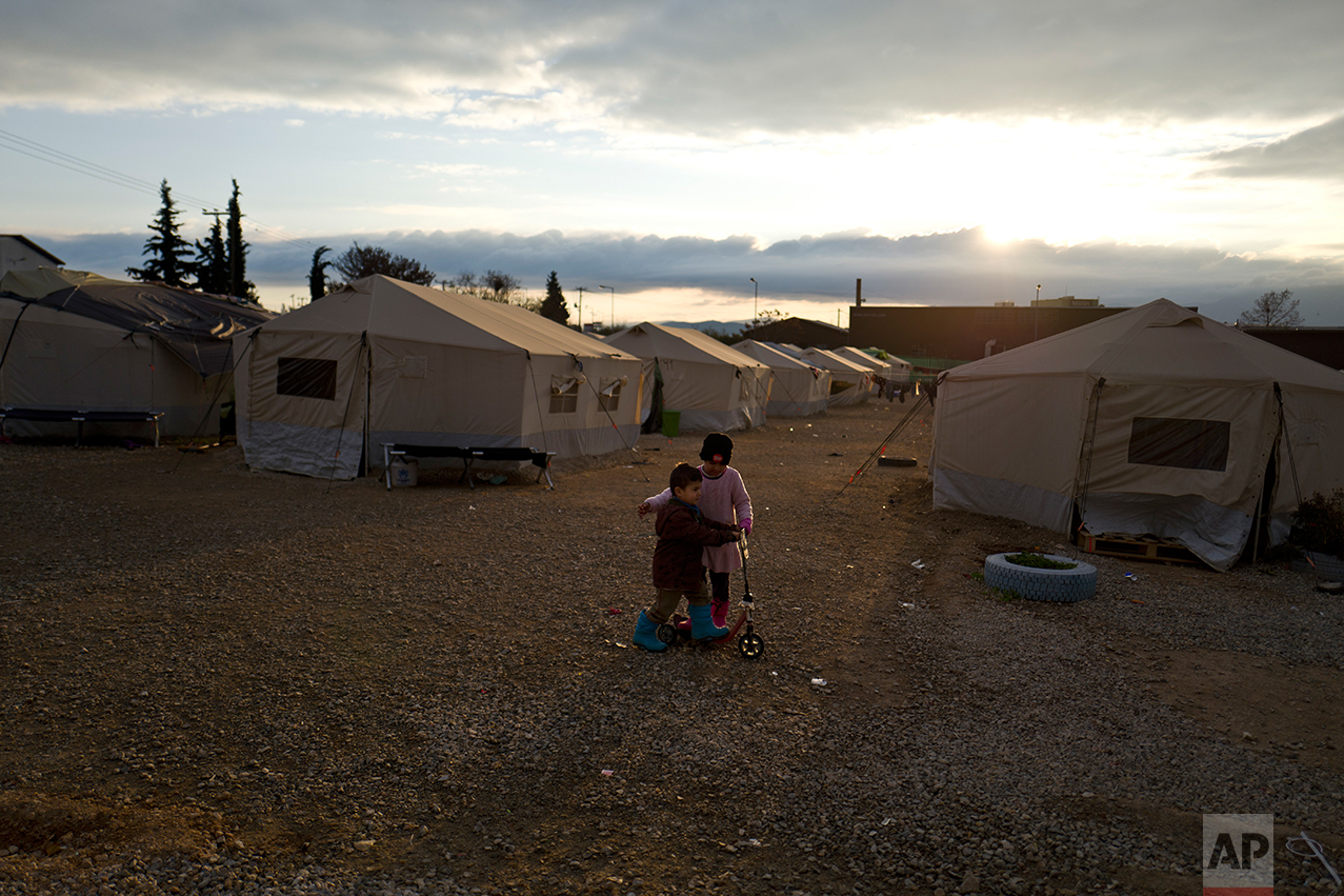 Afghan refugee Nagina Hafizullah, 6, teaches her younger brother Omar, 4, how to ride a scooter near their family's tent at the refugee camp of Oinofyta about 58 kilometers (36 miles) north of Athens, Tuesday, Dec. 27, 2016. (AP Photo/Muhammed Muheisen)