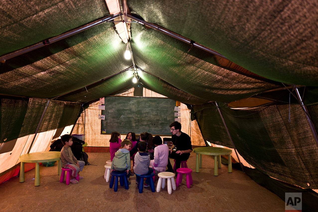 Afghan refugee children gather around two volunteering teachers during a class at a makeshift school in the refugee camp of Oinofyta about 58 kilometers (36 miles) north of Athens, Tuesday, Dec. 27, 2016. (AP Photo/Muhammed Muheisen)