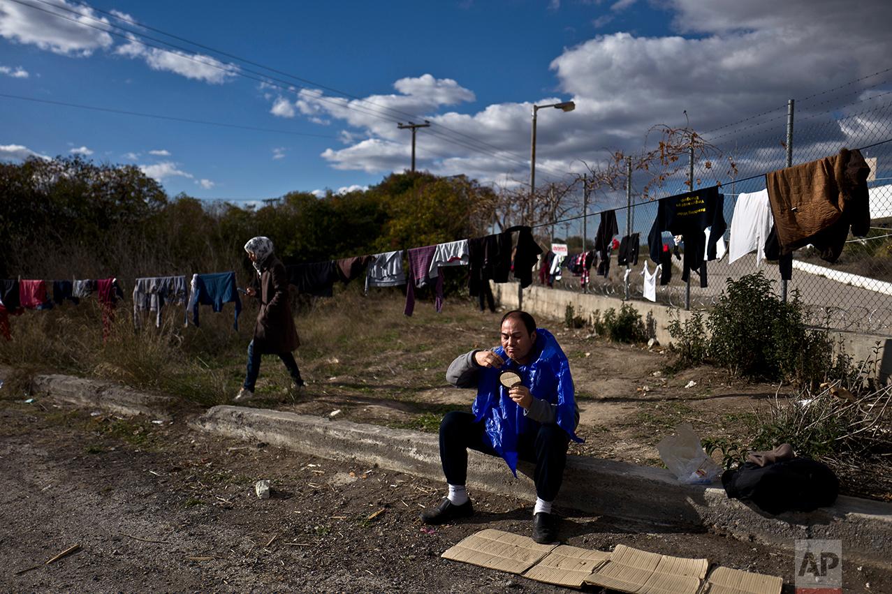 Afghan refugee Ghullam Tahiri, 40, trims his beard at the refugee camp of Oinofyta about 58 kilometers (36 miles) north of Athens, Monday, Dec. 26, 2016. (AP Photo/Muhammed Muheisen)