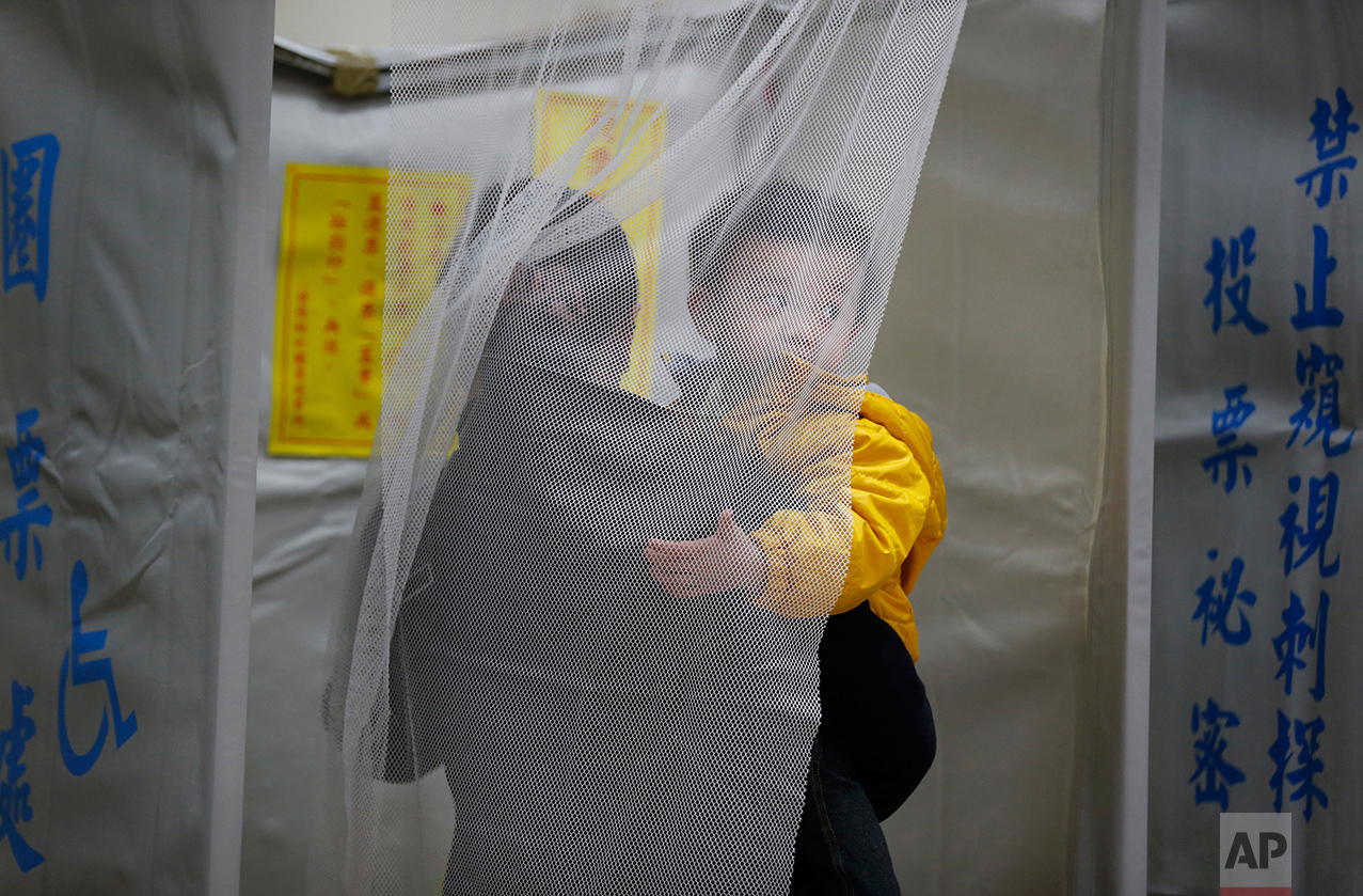 A Taiwanese woman marks her ballots while holding her son in the presidential election at a local polling station in Taipei, Taiwan, Saturday, Jan. 16, 2016. (AP Photo/Wally Santana)