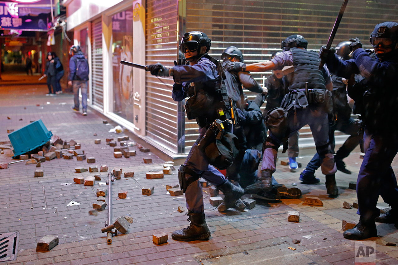 Riot police officers react as protestors set fires and throw bricks at them in Mong Kok district of Hong Kong, Tuesday, Feb. 9, 2016. Hong Kong's Lunar New Year celebration descended into chaotic scenes as protesters and police clashed over a street market selling fish balls and other local holiday delicacies. (AP Photo/Vincent Yu)