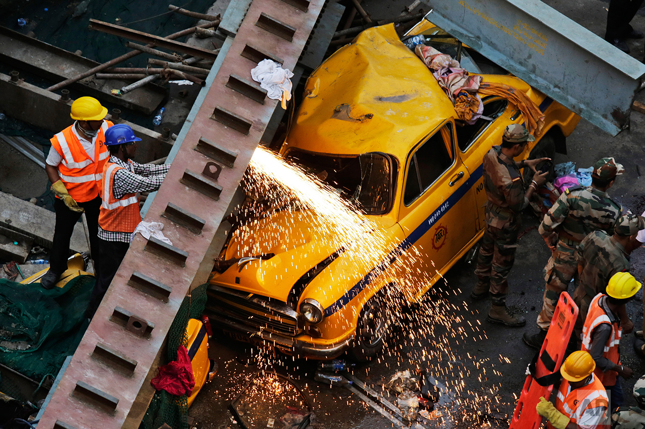 Rescue workers cut through parts of a partially collapsed overpass in Kolkata, India,Thursday, March 31, 2016. (AP Photo/Bikas Das)