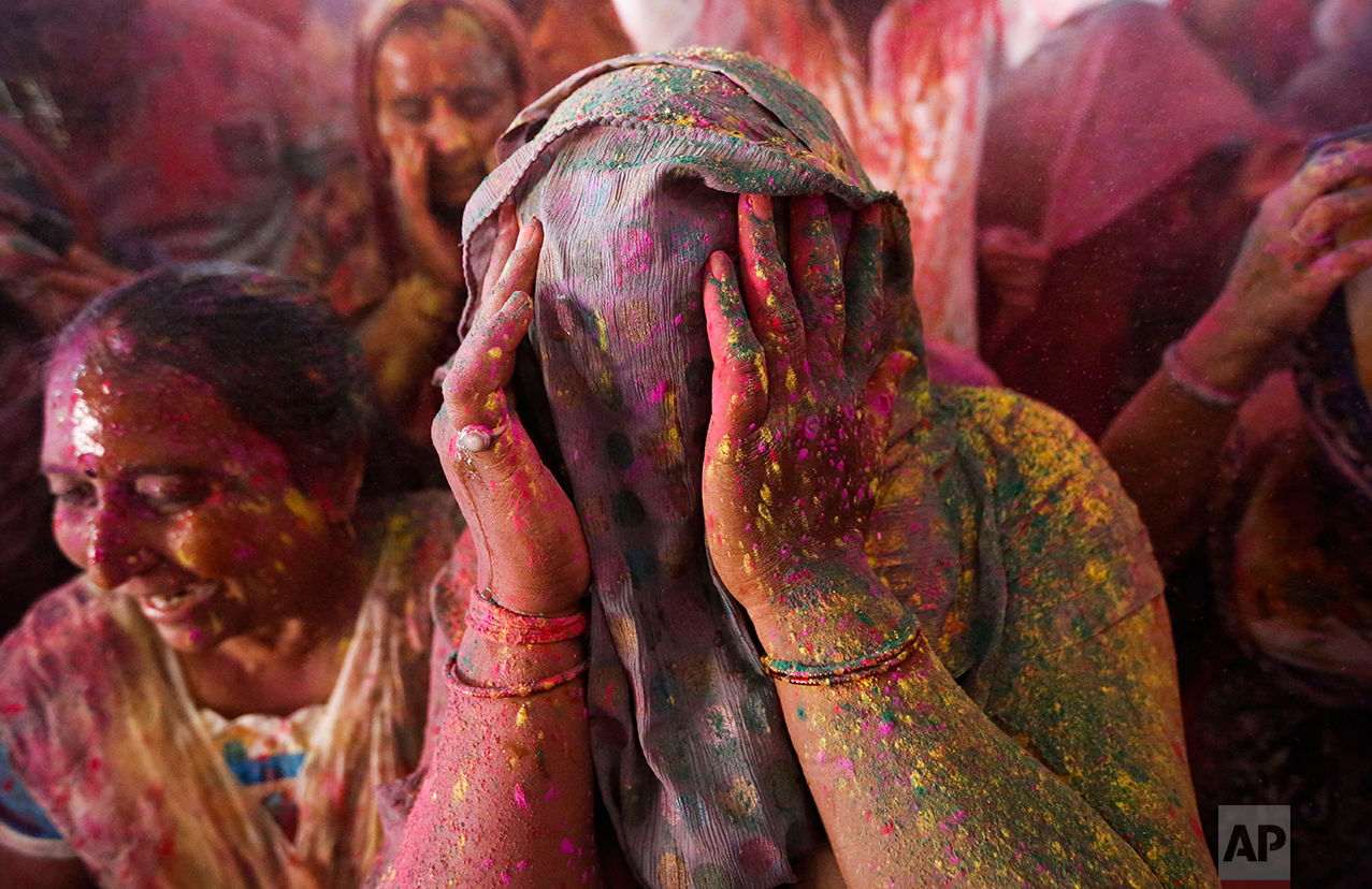 An Indian woman covers her face during Holi celebrations, the Hindu festival of colors, in Ahmadabad, India, Wednesday, March 23, 2016. (AP Photo/Ajit Solanki)