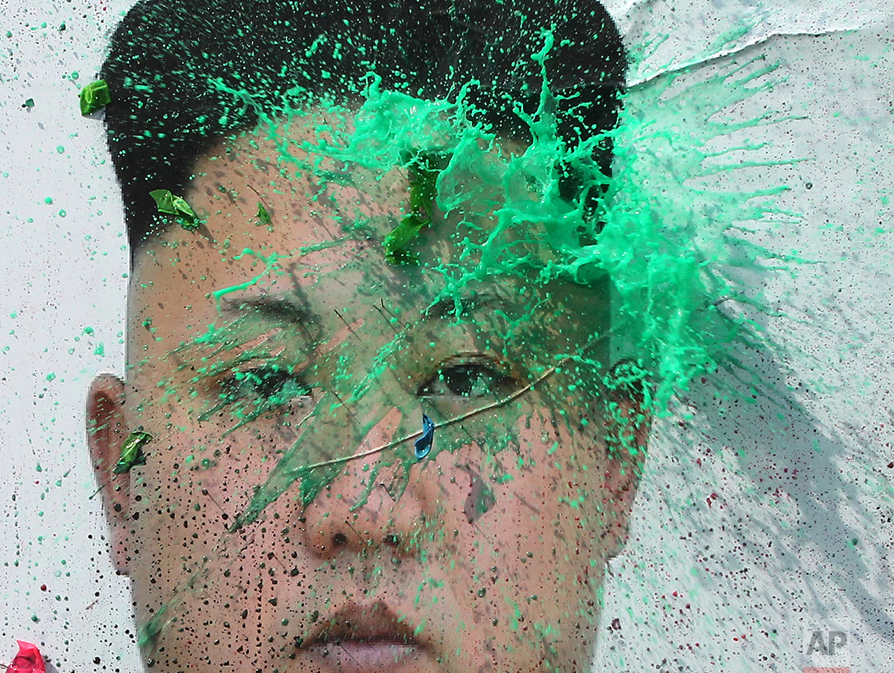 A balloon thrown by a North Korean defector containing a colored liquid bursts on a portrait of North Korean leader Kim Jong Un during a rally protesting North Korea Wednesday, March 30, 2016, in Seoul, South Korea. (AP Photo/Ahn Young-joon)