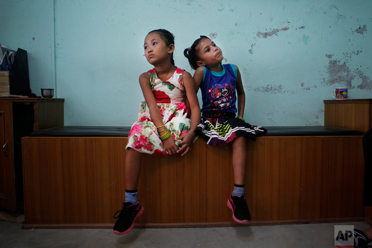 In this Sept. 8, 2015 photo, best of friends Khendo Tamang, left, and Nirmala Pariyar, both 8, wait to be measured for a new prosthetic legs in Kathmandu, Nepal. The girls became close friends while in recovery after each one lost a leg in Nepal's massive April 25, 2015 earthquake that killed nearly 9,000 people dead and more than 22,000 injured. (AP Photo/Niranjan Shrestha)