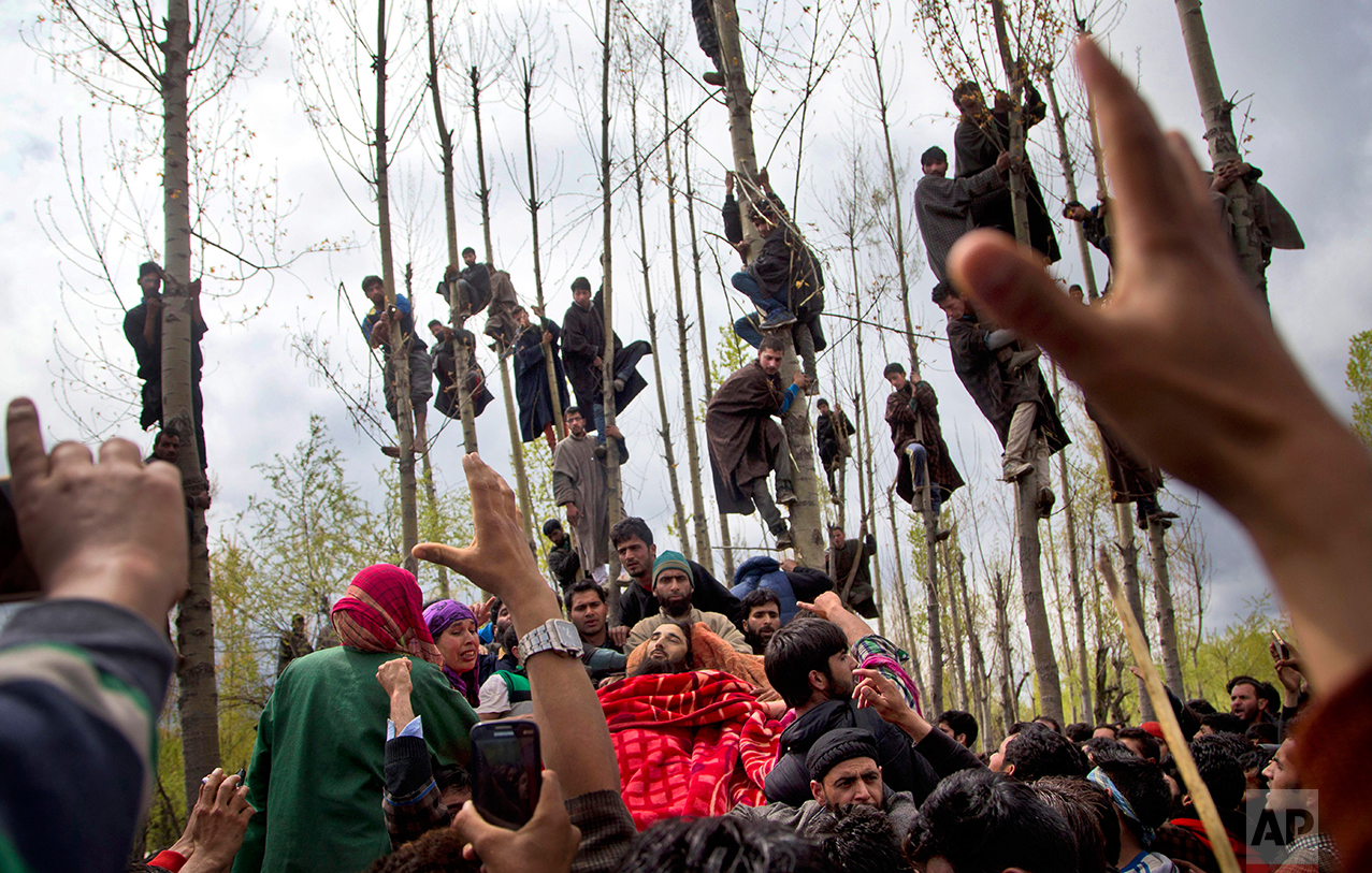 Kashmiri Muslims try to get the glimpse of the body of Waseem Malla, a suspected militant of Hizbul Mujahideen, during his funeral procession in Pehlipora, some 60 kilometers (35 miles) south of Srinagar, Indian controlled Kashmir, Thursday, April 7, 2016.  (AP Photo/Dar Yasin)