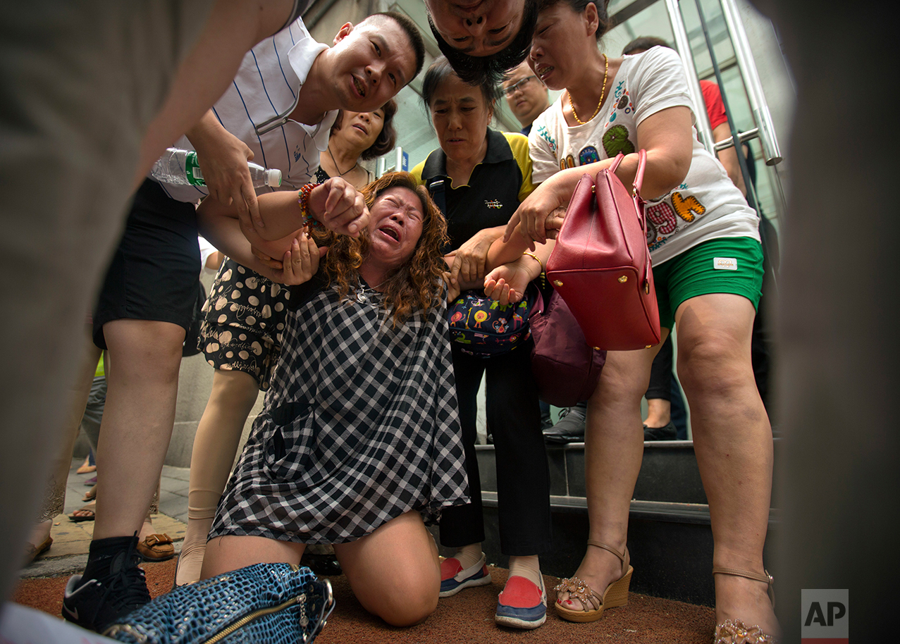 A woman cries while while demonstrating with relatives of passengers aboard Malaysia Airlines Flight 370 outside the Ministry of Foreign Affairs in Beijing, China, Friday, July 29, 2016. (AP Photo/Mark Schiefelbein)